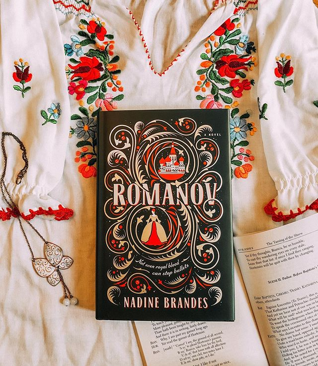 "WHAT ARE YOU READING? 📚 I'm only 64 pages into ""Romanov"" by @nadinebrandes , and I'm already in love with the story. Revolutionary Russia + magic = PURE BLISS 😍  While reading about Nastya and Zash, I want to sip borchst and listen to Dario Marianelli's Anna Karenina soundtrack.  Oh, how the book takes me back to my adventures in Eastern Europe. The closest I got to Russia was Kraków, Poland (hence the embroidered smock and handcrafted pendant). Still, I experience major Old World vibes from dear ""Romanov."" Nadine stuns with her vivid descriptions and impish, lovable heroine. I can't wait to see where the story goes!! 🙌🏻 ———————————————————- A new post is on my blog! Title... Not a Blogger: 5 Non-Blog Ways to Create Content and Grow Platform. Yes, my anti-blog post is posted on my blog. Cue Caroline roast. 🙈🤣 In all seriousness, the article shares valuable author PR and branding tips. Click the link in my bio to read. ———————————————————- Also, I will be part of the faculty for the 2019 Florida Writing Workshop, a one-day writers conference in Tampa with agents, sessions, and critiques -- happening June 8, 2019. Come say hi!! ♥️ * * * * * *  #May #lifestyleblogger #aesthetic #lifestylephotography #photography #writing #author #blogger #instagood #authorsofinstagram  #amwriting #bookstagram #reader #bookblogger #writersofinstagram #booknerd #reading #lifestyle #digitalnomad #shelfie #bookbox #creativelifehappylife #amreading #writer #thatsdarling #bookhaul #layout #madisonrosepresets #bookworm"