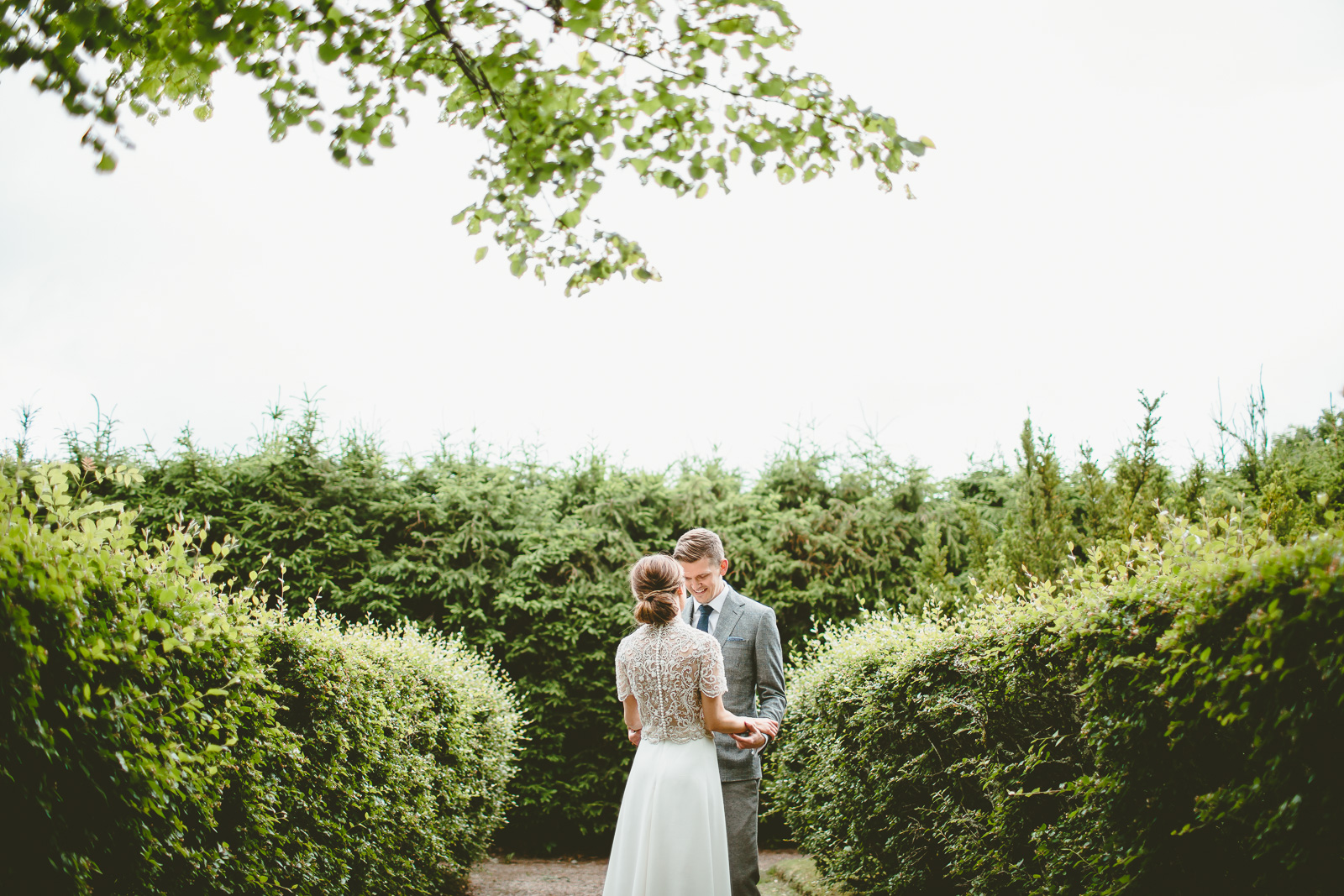 First look - Cloudy day - Hedges converge around them drawing you towards the couple, while the overhead tree breaks up the empty sky.