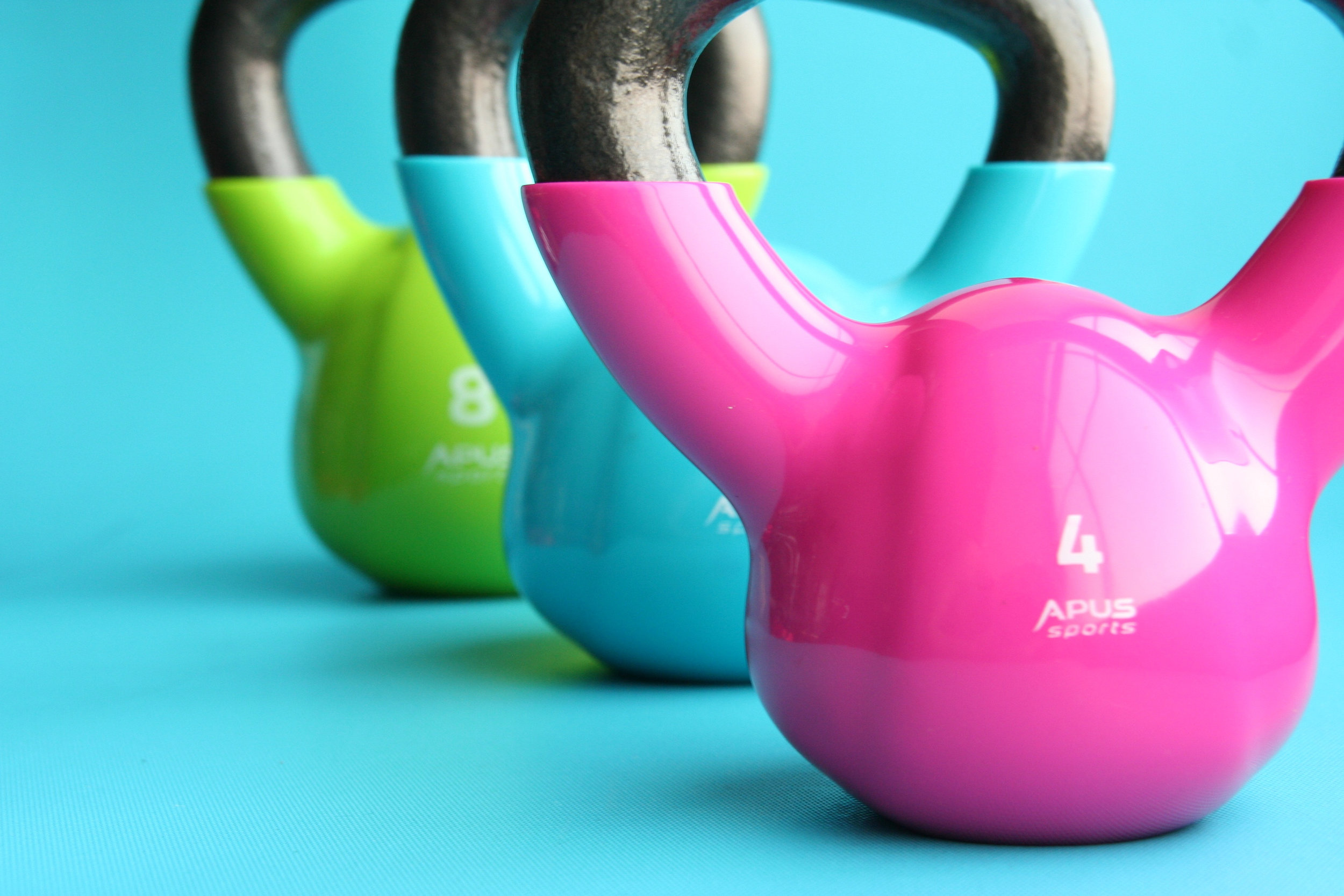 Canva - Green, Blue, and Pink Kettle Bells on Blue Surface.jpg