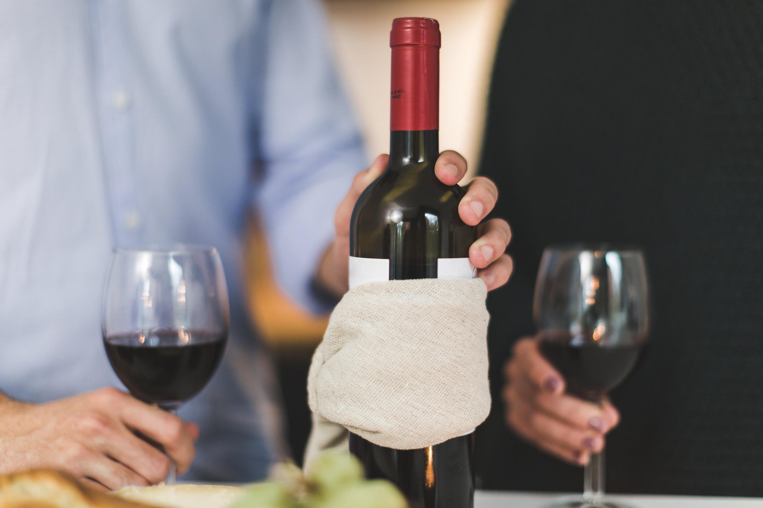 Canva - Man Holding White Labeled Red Wine Bottle Near Wine Glasses.jpg