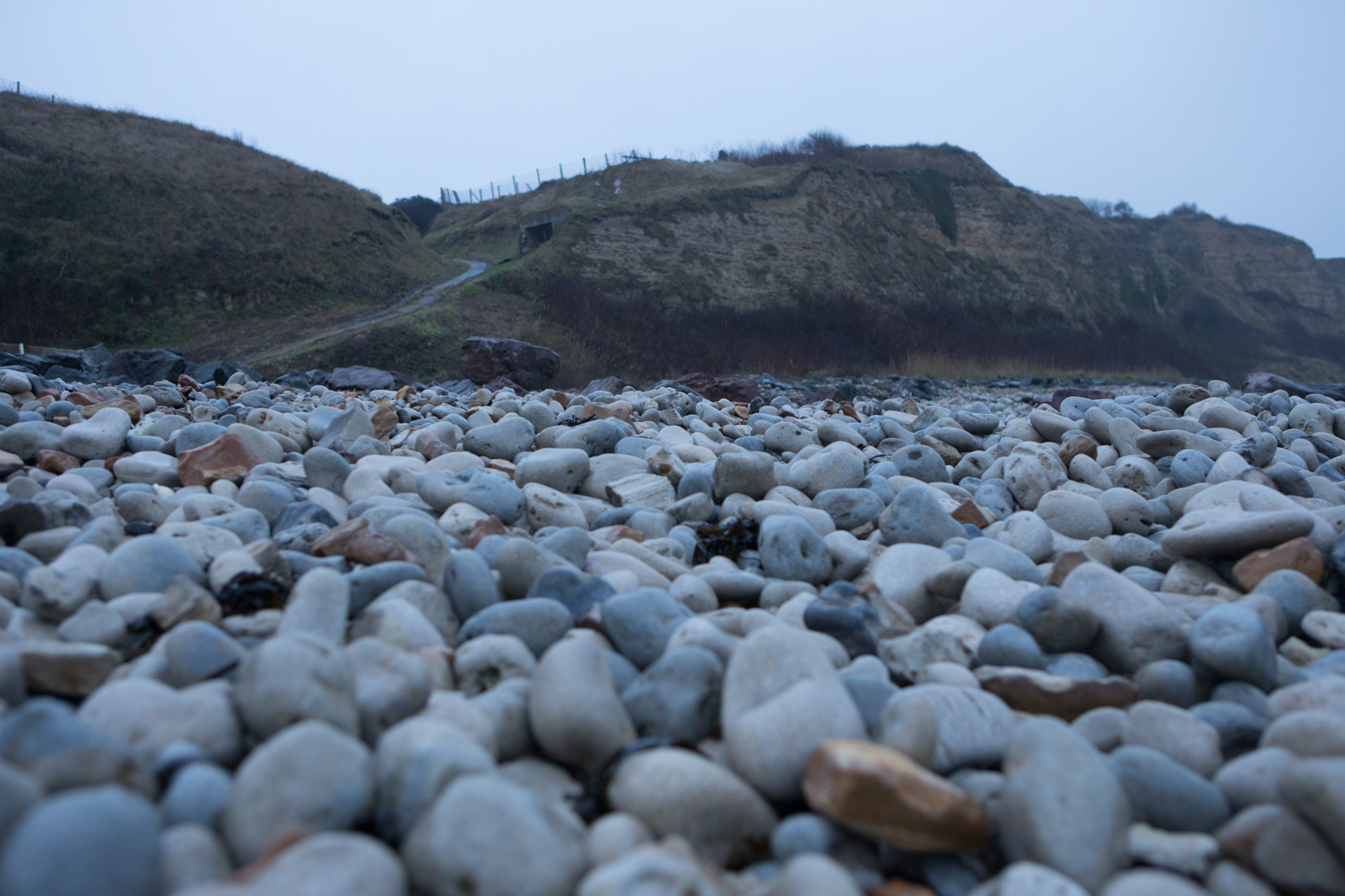 Omaha Beach: Shingle level view of the cliffs overlooking Omaha and part of the extensive defensive network. Right before the curve in the path off the beach there is a defensive position. These positions were often times placed to face parallel to the beach rather than facing the ocean. This made any fire from the position more difficult to spot from the sea side and harder for off-shore batteries to target. )Part of Omaha is what is referred to as a shingle beach (i.e. covered in rocks).)