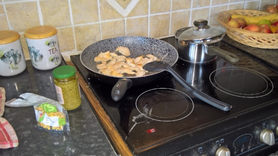 Making chicken-pesto pasta with pine nuts.