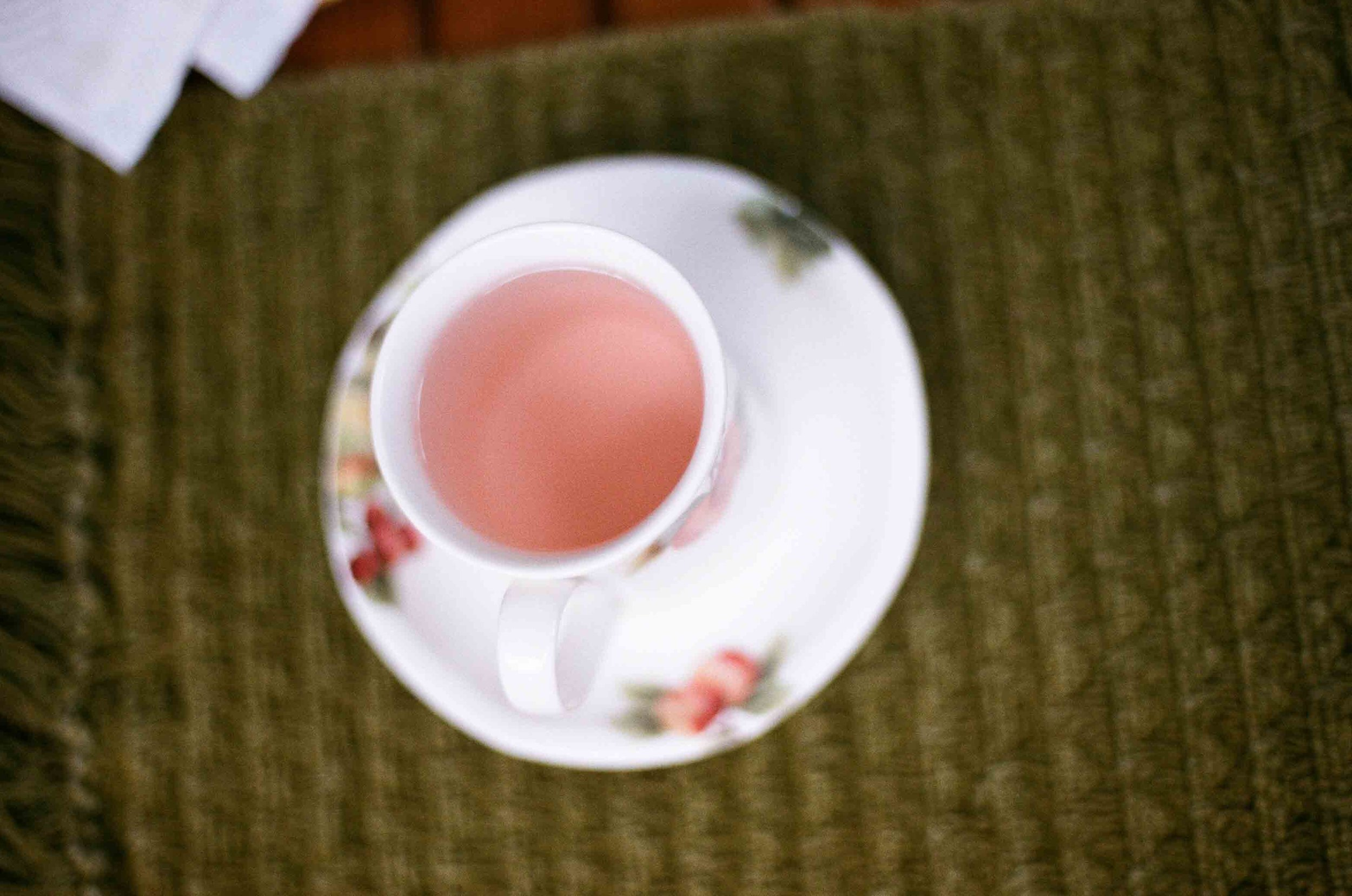 Strawberry tea made by steeping the leaves and adding a strawberry fruit for color.