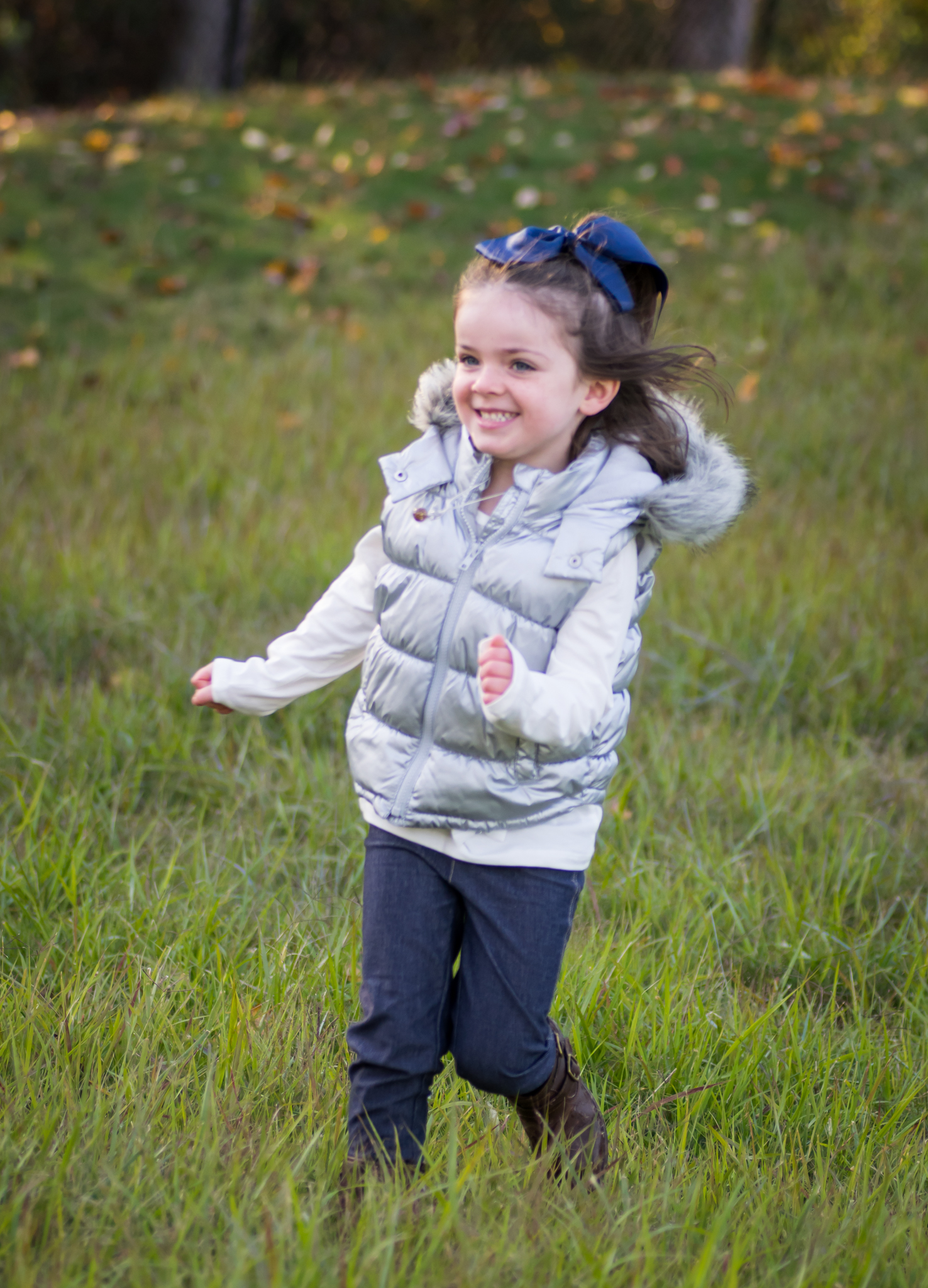this is an image of a little girl running in the grass and smiling as she runs towards her mom