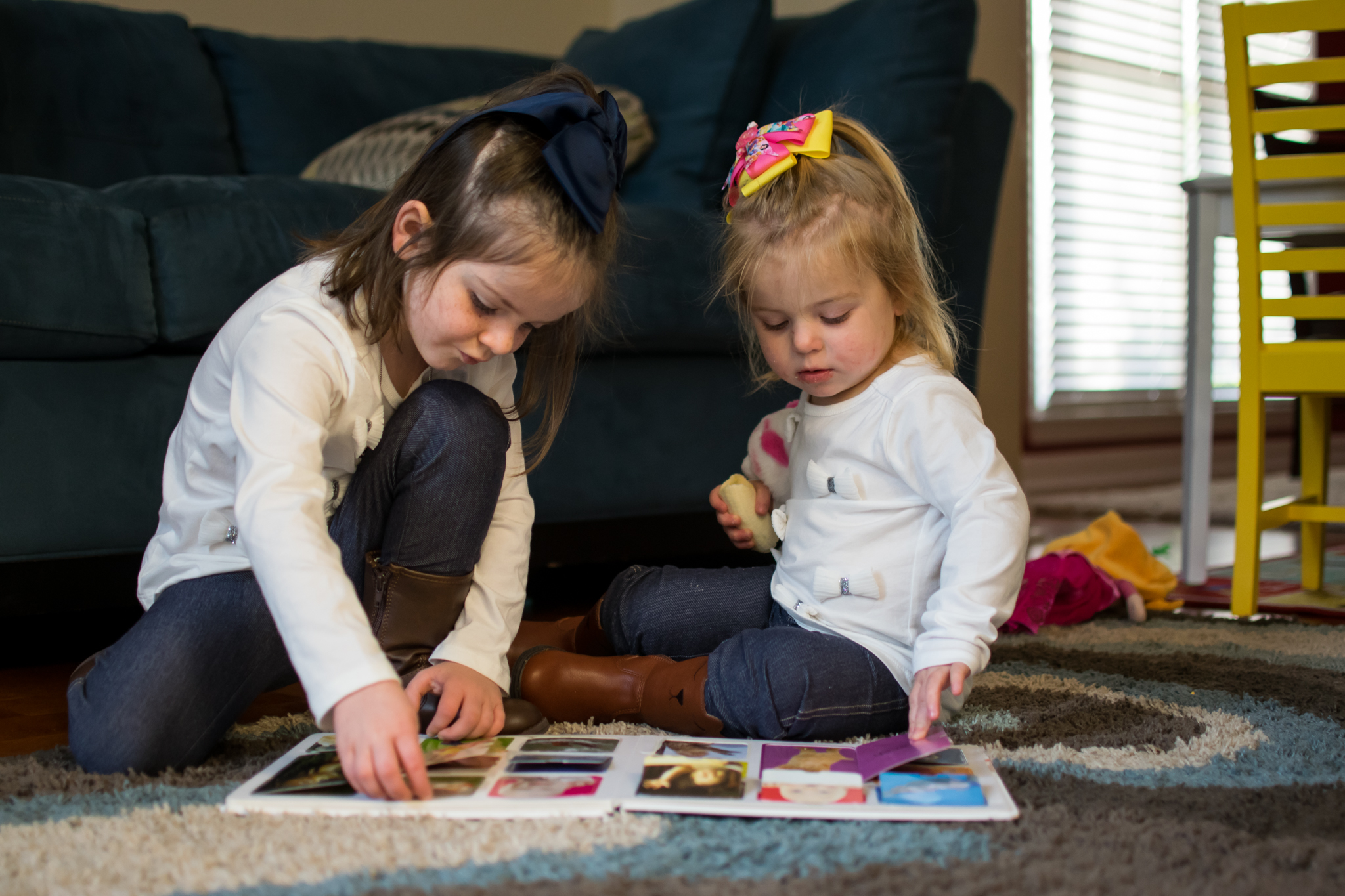this is an image of two little girl sisters sitting on the floor and reading a book