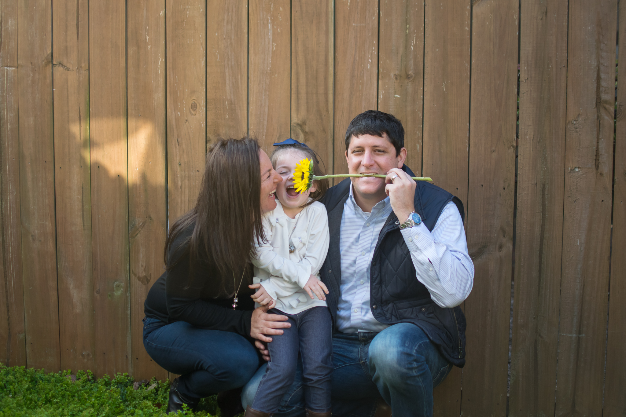 this is an image of a father holding a flower in his mouth, while the young girl and her mom are laughing