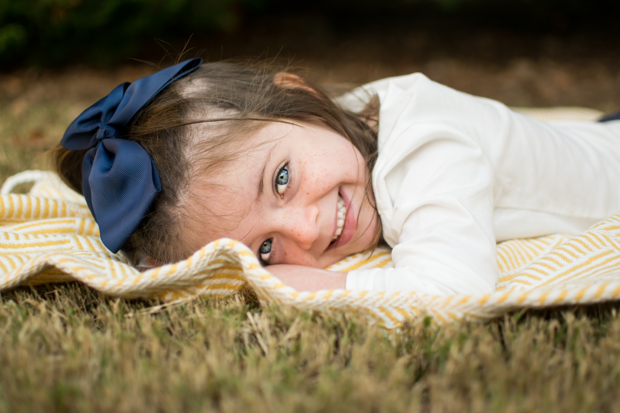 this is an image of a young girl laying on a blanket outside and smiling