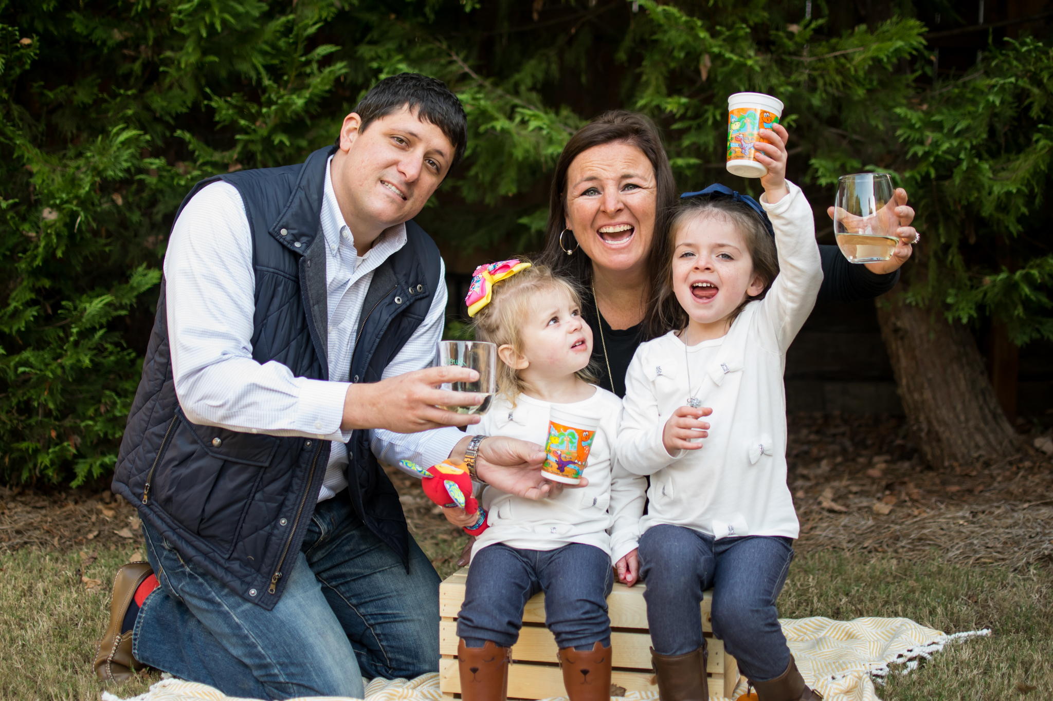 this is an image of a family of four- mother, father, two young girls holding up drinks and making a cheer