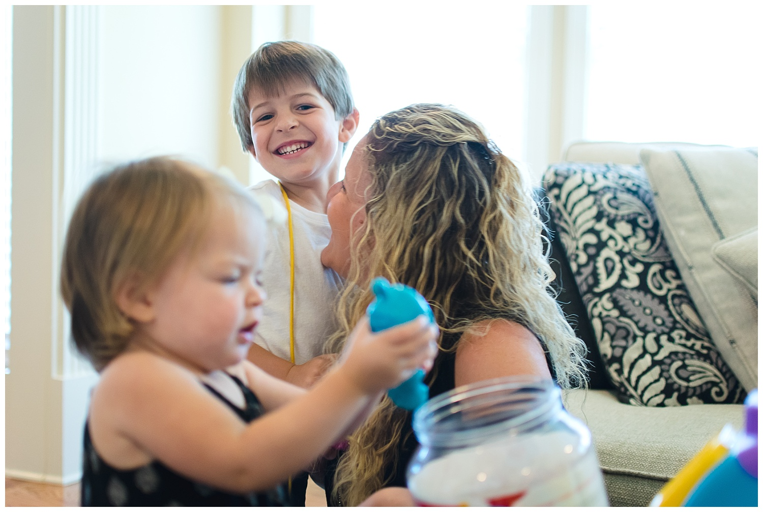 this is an image of a young girl playing with her toys in the foreground and mom playing with another young child in the background in their home