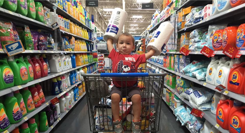 little boy riding in walmart cart with paper towels on his arms