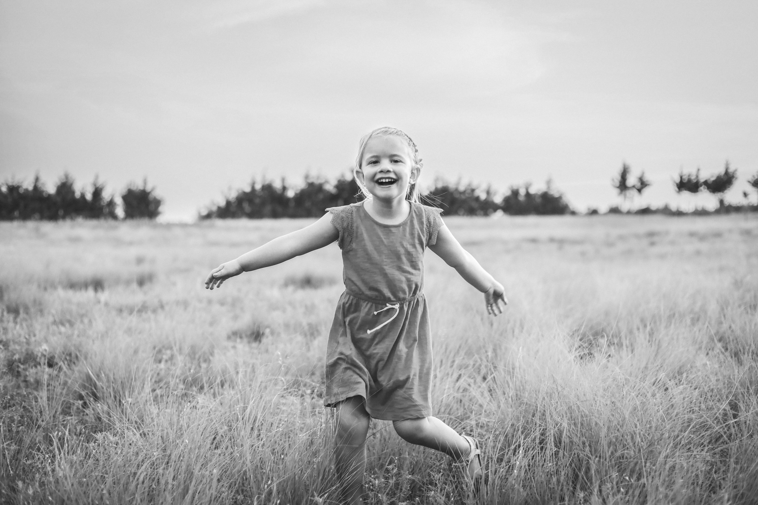 Black and white photo of little girl dancing in a field in Stillwater, Oklahoma.