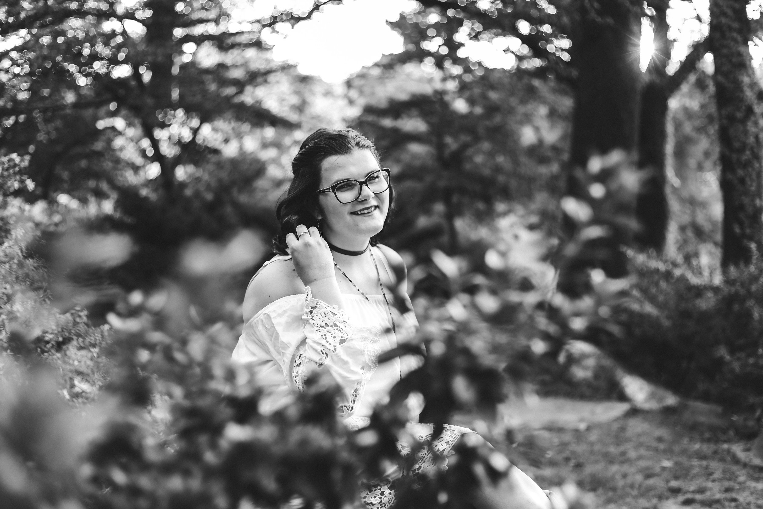 Black and white photo of high school senior girl sitting in park in Tulsa.