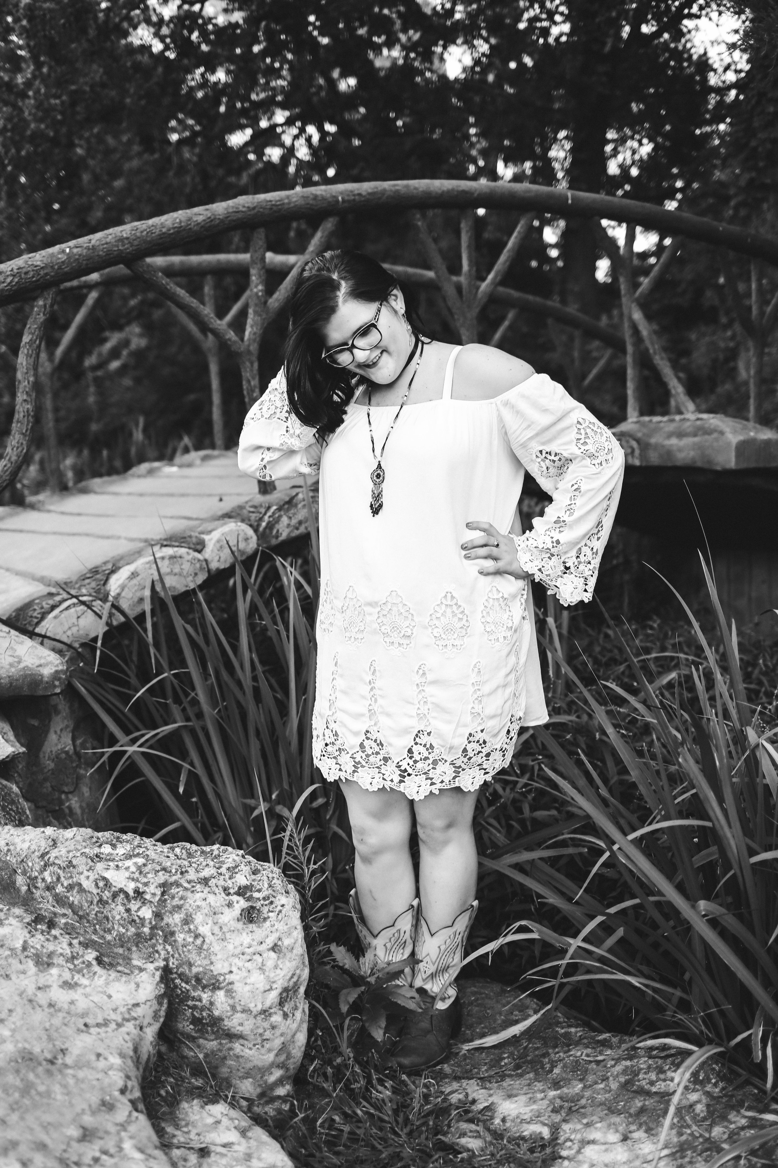 Black and white images of high school girl wearing dress and boots standing in front of wooden walking bridge at Woodward Park in Tulsa.