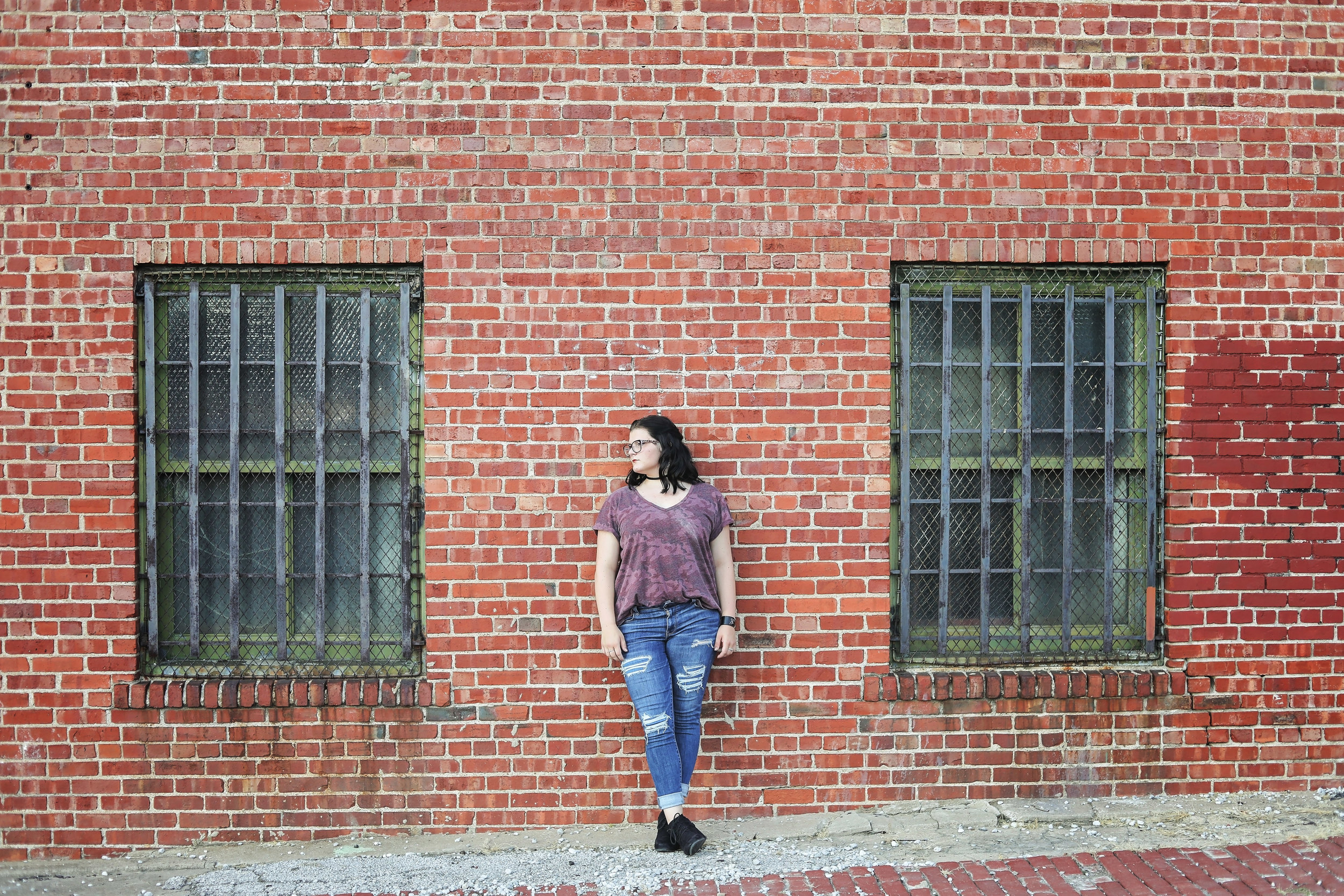 High school senior wearing jeans and black boots standing against a brick wall with windows on both sides of her in downtown Tulsa.