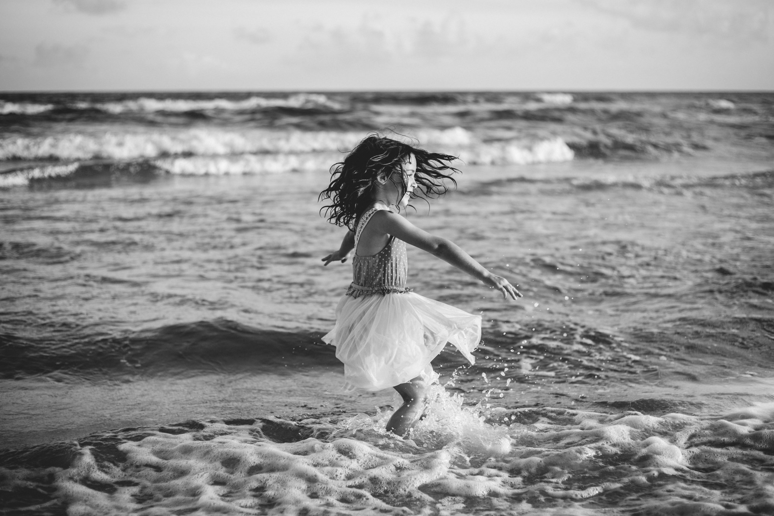 Black and white photo of little girl dancing in the ocean in Orange Beach, Alabama.