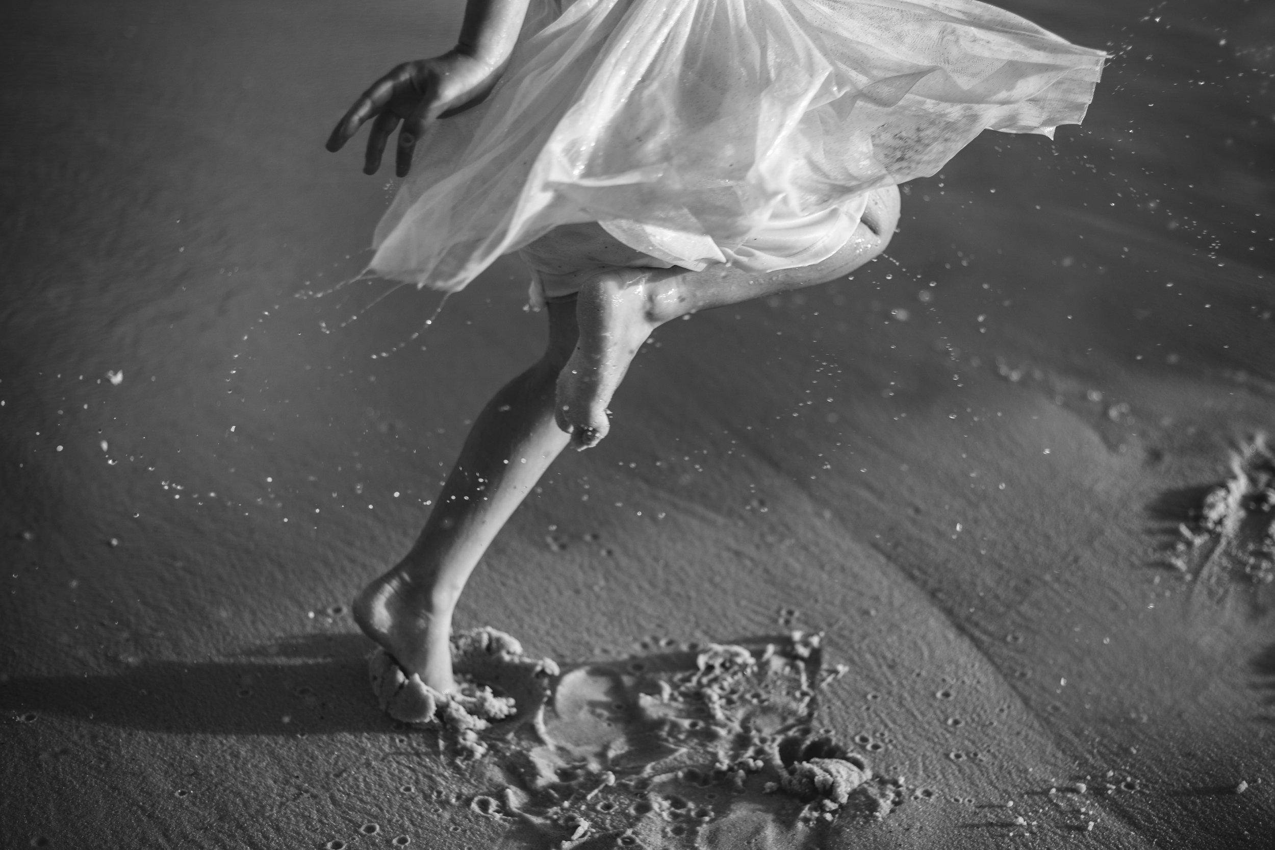 Black and white image of little girls foot dancing in the sand at the beach.