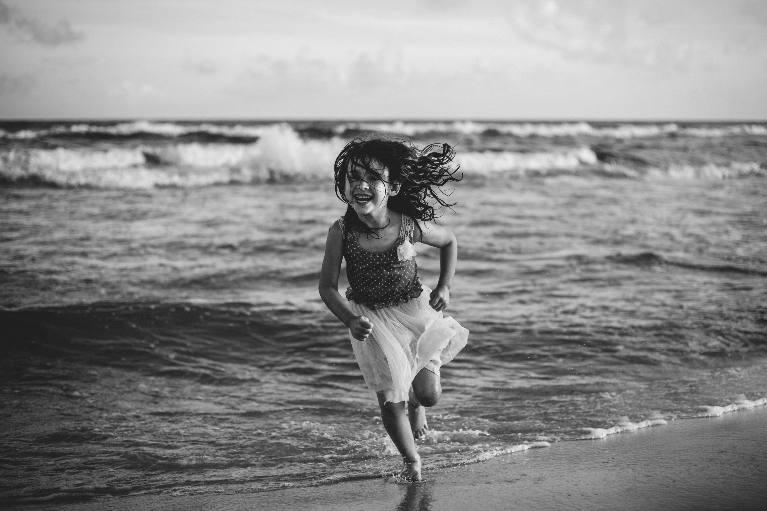 Black and white image of little girl wearing dress running out of the ocean at Orange Beach Alabama.