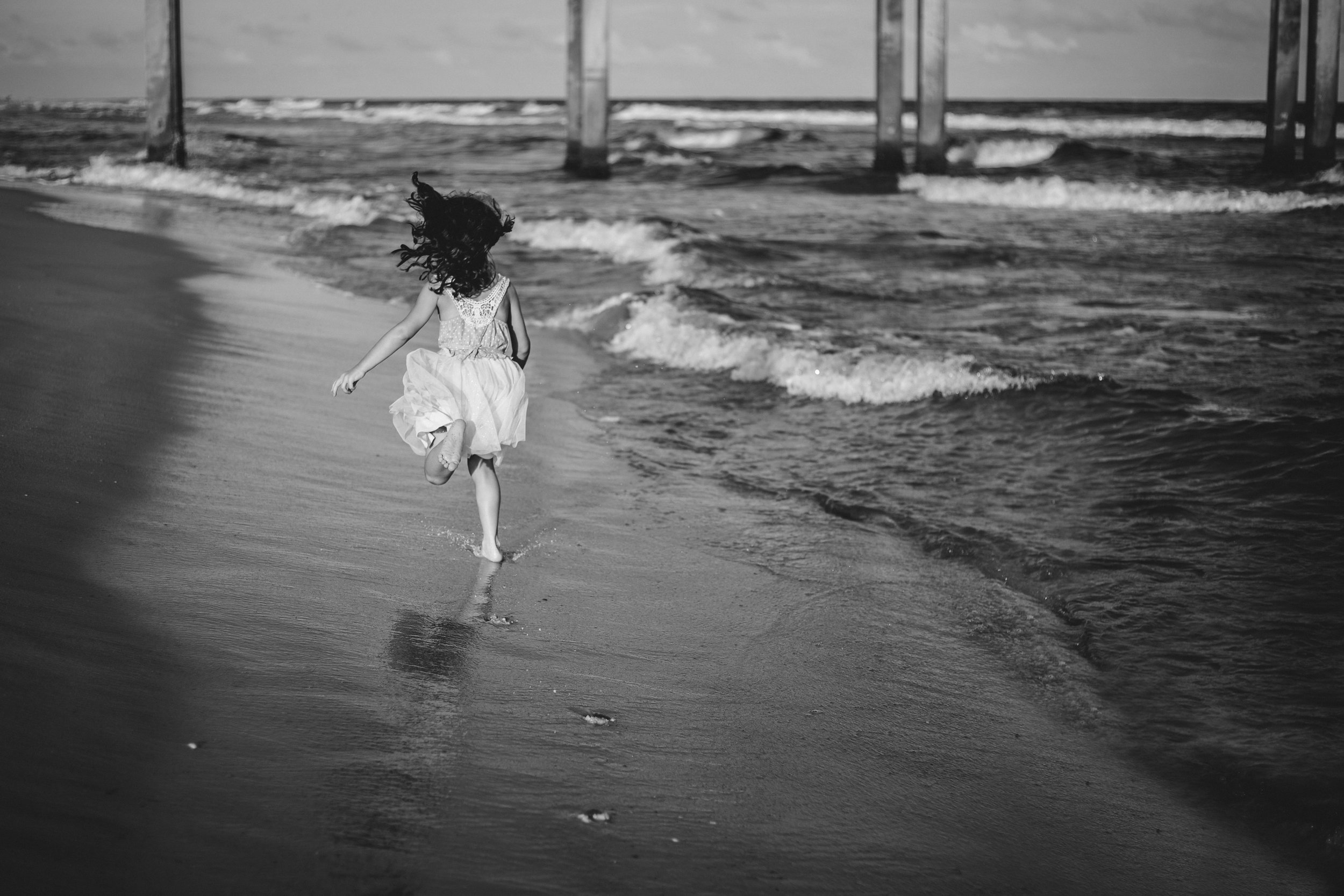 Black and white image of little girl running down the beach.