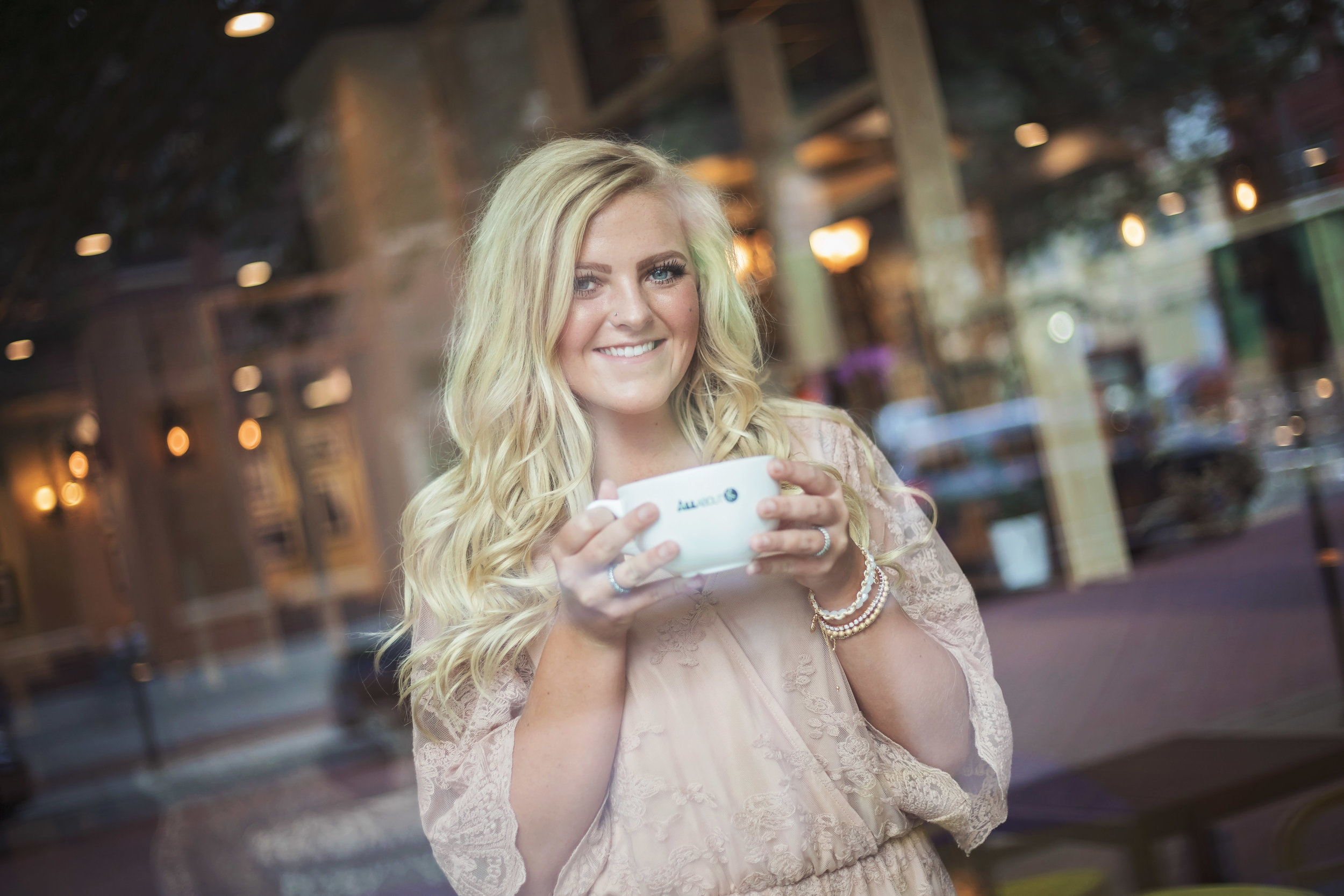 High School senior girl with long blonde hair sitting inside a coffee shop, holding a white coffee mug.