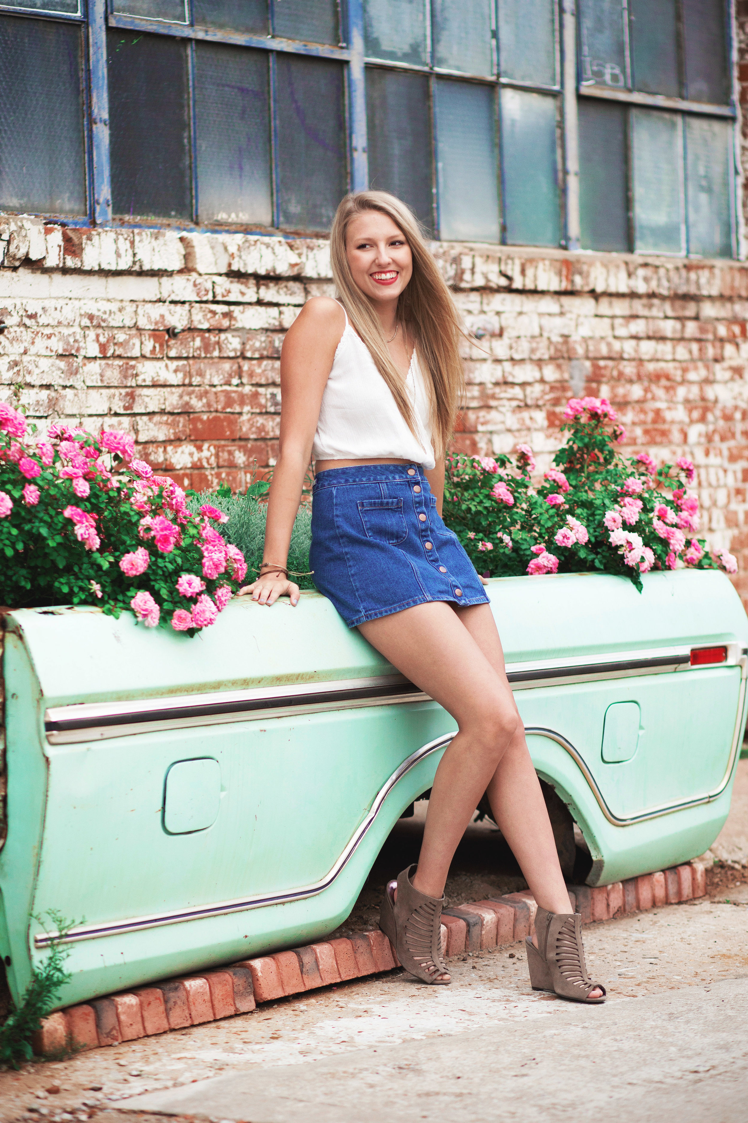 High school senior girl wearing a mini skirt leaning against old pick up bed in an alley in Oklahoma City.