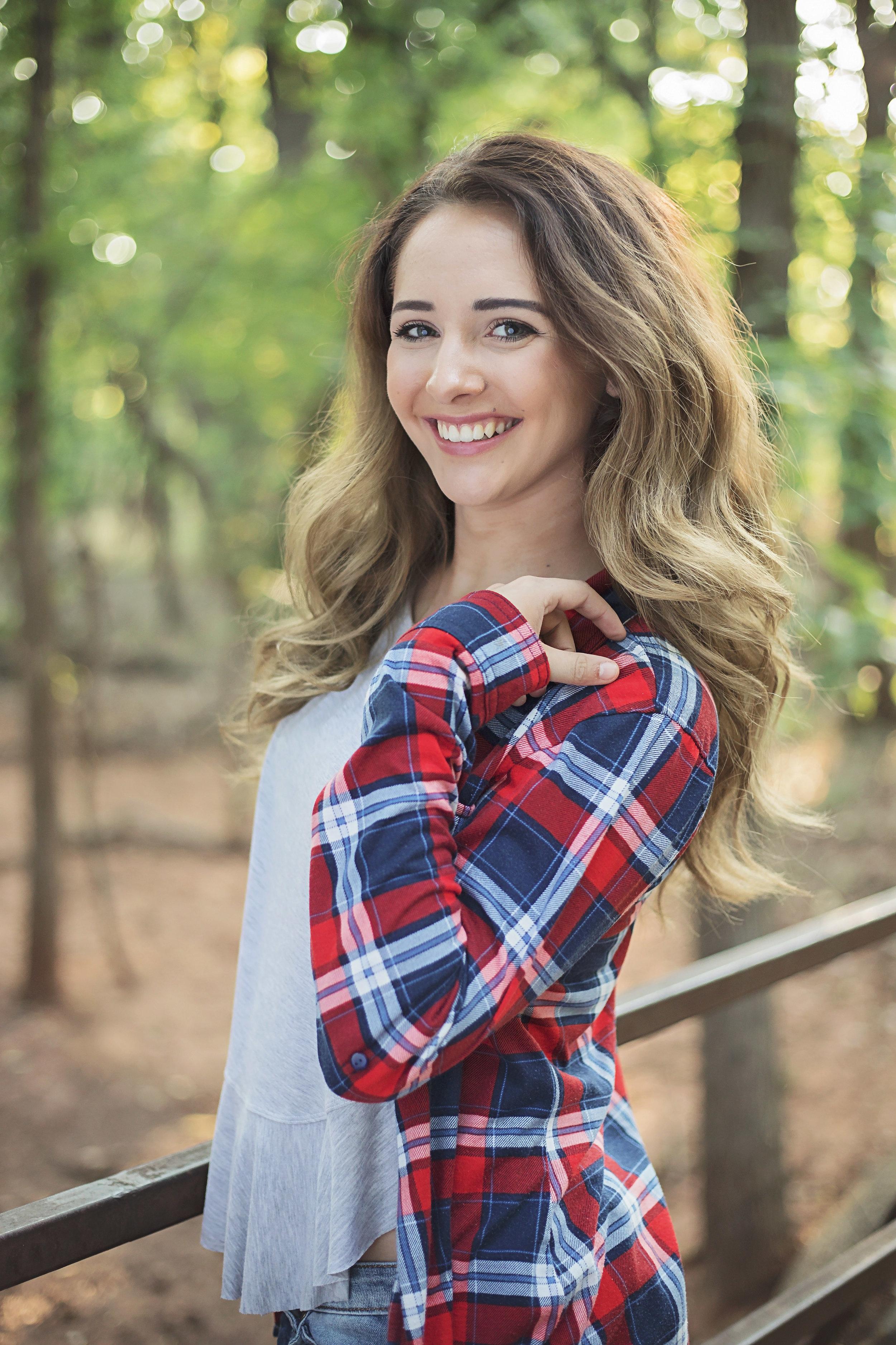 High school senior girl wearing red flannel at park in Oklahoma City. Oklahoma Senior Photographer Amanda Lynn.