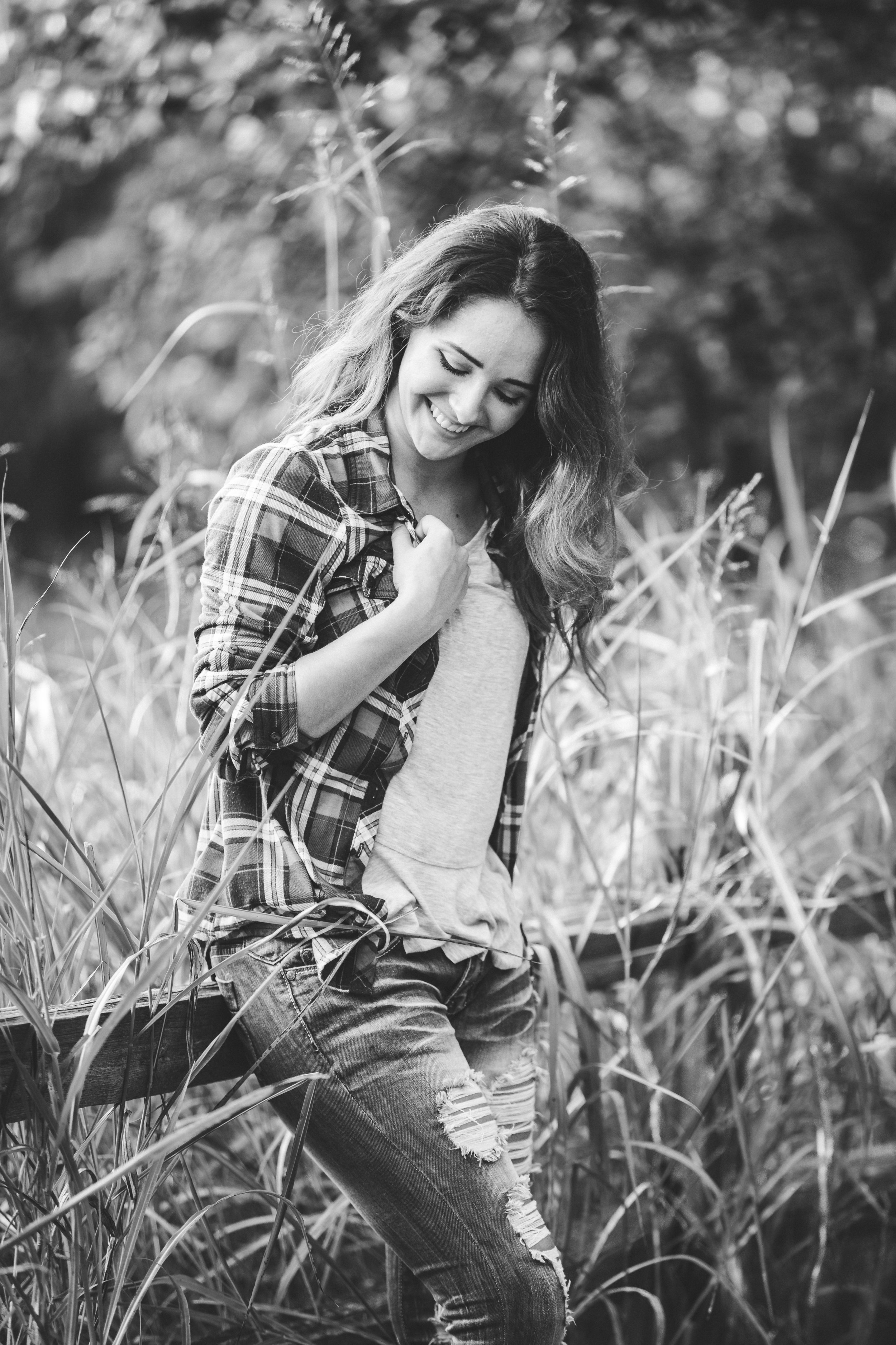 Black and white image of senior girl with long hair laughing and looking down while leaning against a wooden fence. Amanda Lynn Oklahoma Senior Photographer.