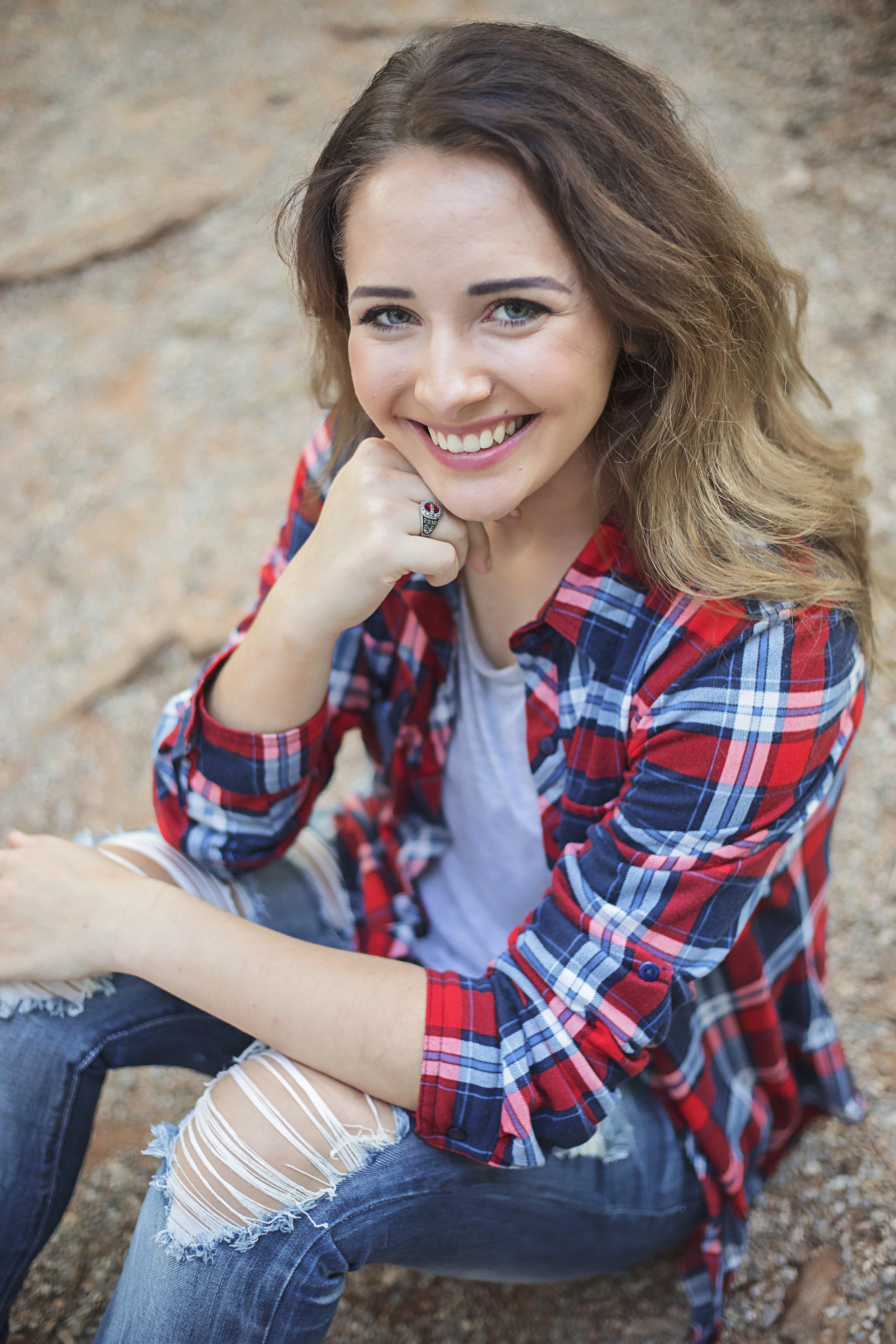 High School Senior Portrait of girl with long brown hair wearing flannel sitting on rock pathway at a park in Oklahoma City. Amanda Lynn Oklahoma Senior Photographer.