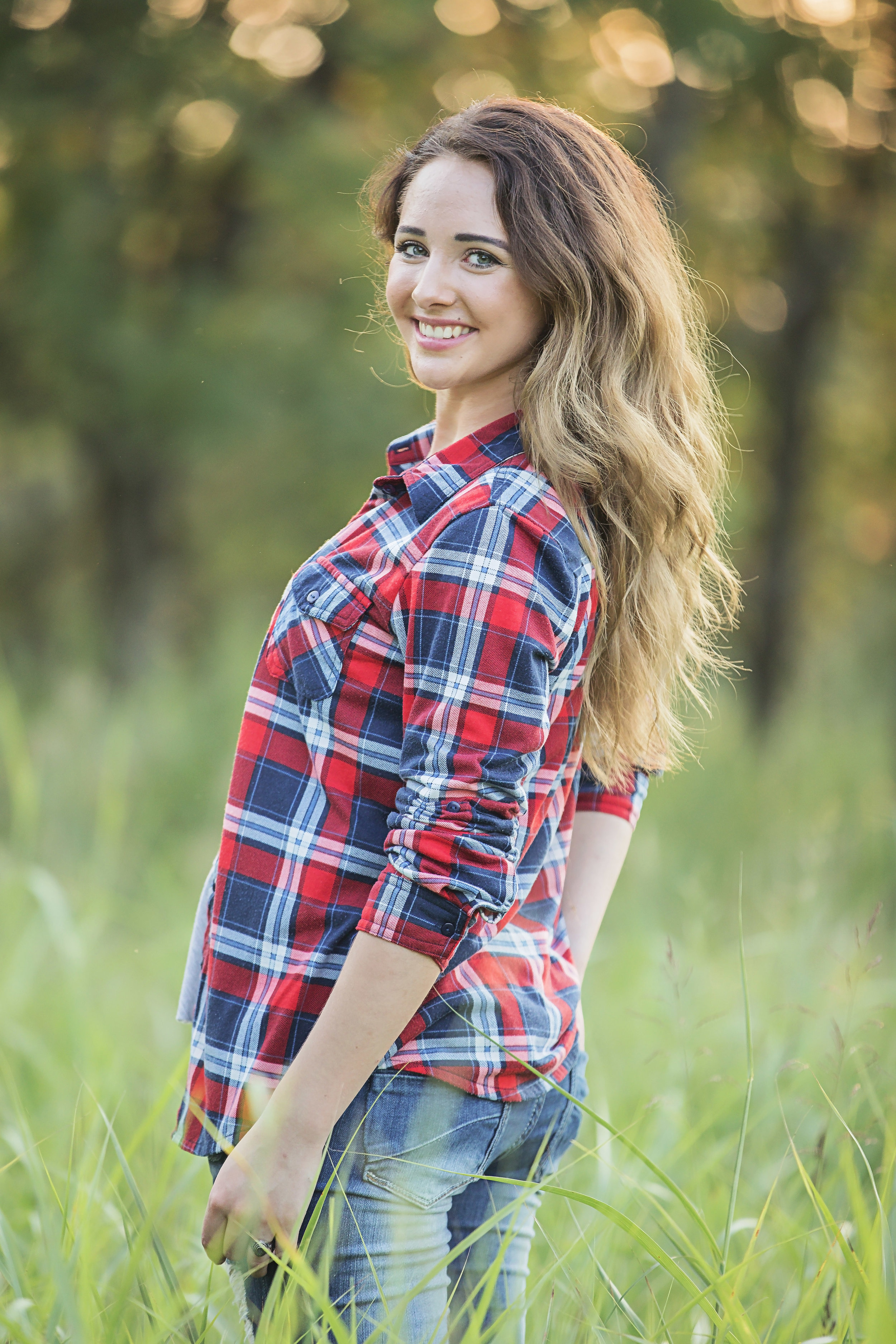 High School Senior girl standing in tall grass in an open field at Oklahoma City park.