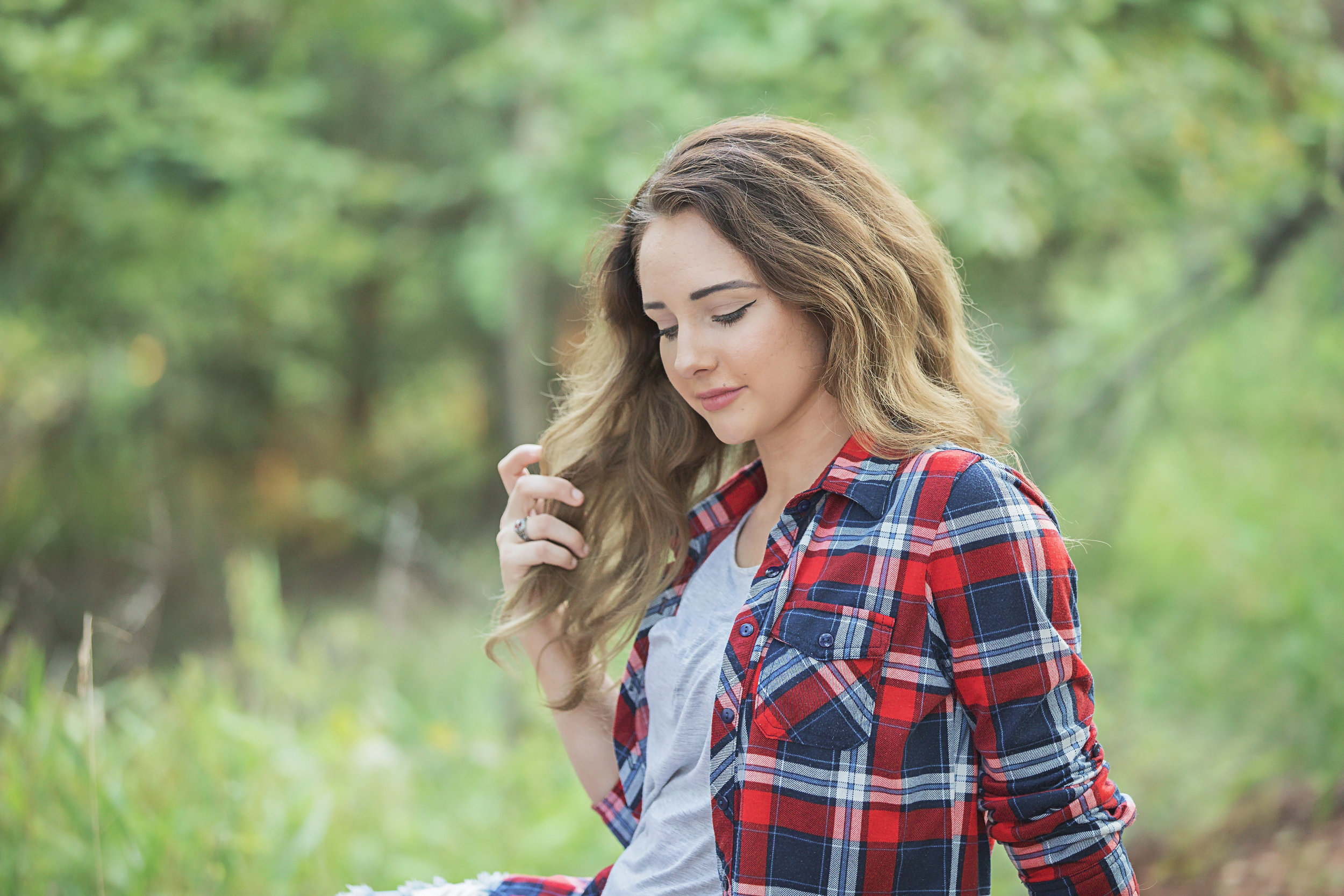 Color image of high school senior girl playing with her long brown hair and looking down. Amanda Lynn Oklahoma Senior Photographer.