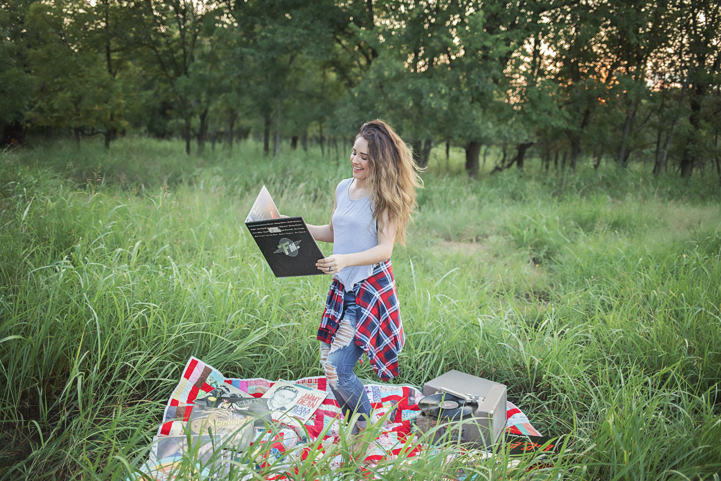 Oklahoma High School Senior dancing on red quilt in an open field in Oklahoma City.