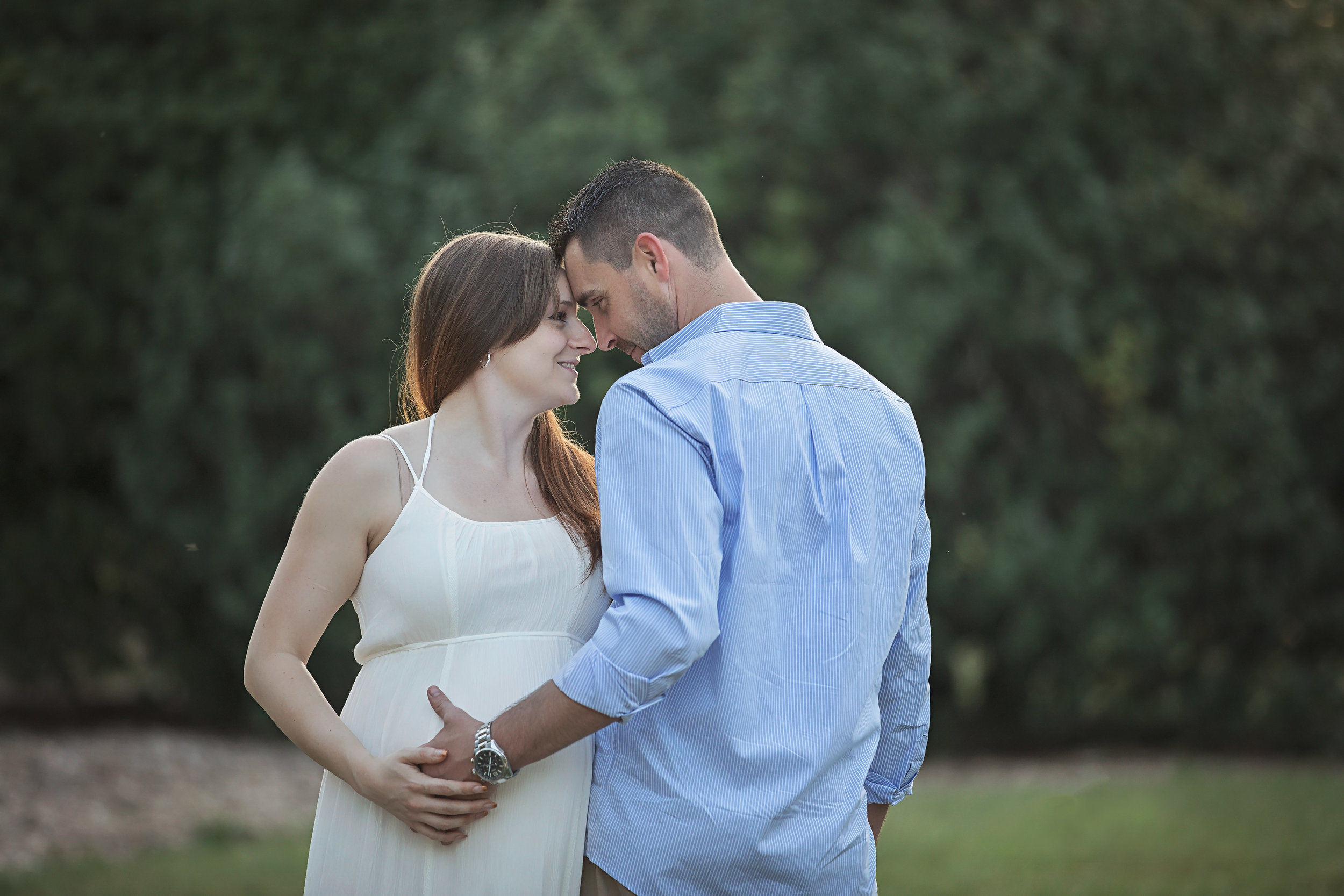 Husband and wife touching foreheads at maternity photoshoot in Oklahoma City.