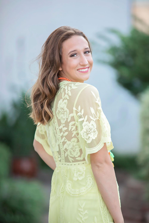 Senior girl wearing orange, looking over shoulder and smiling. Oklahoma Senior Photographer Amanda Lynn.