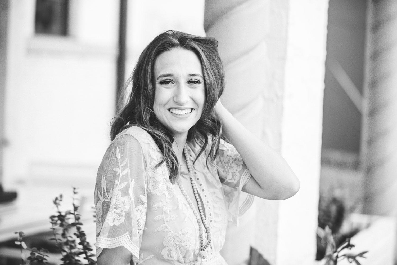 Black and white image of senior girl holding hair against head and smiling at the camera. Oklahoma City Senior Photographer Amanda Lynn.