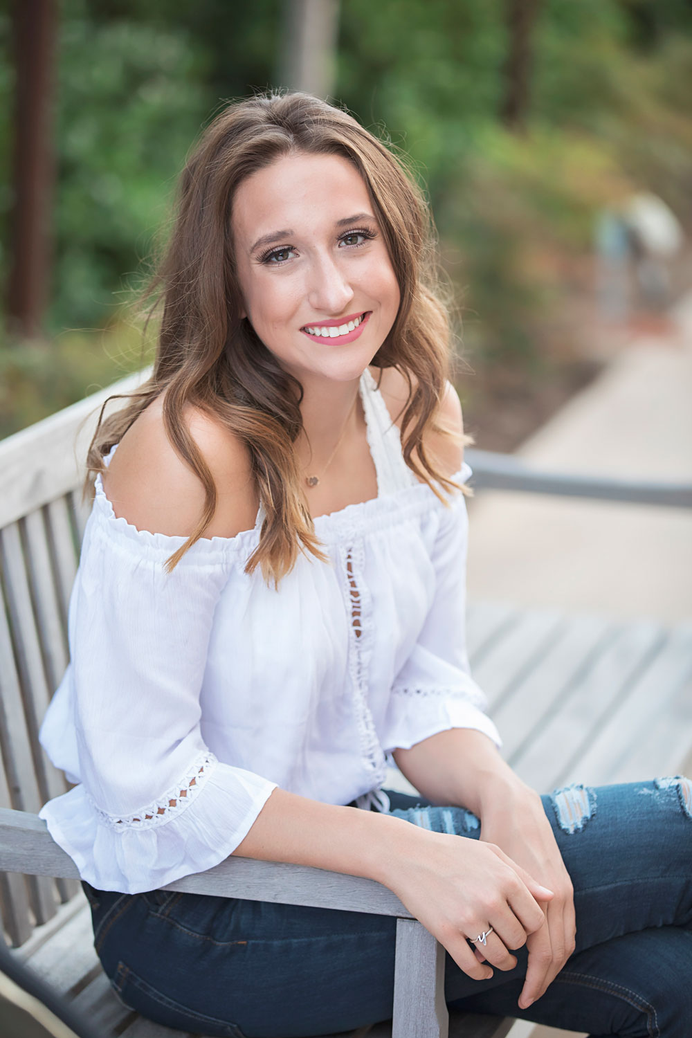 Senior girl wearing white shirt and blue jeans sitting on a bench at the Ambassador Hotel in Midtown Oklahoma City.