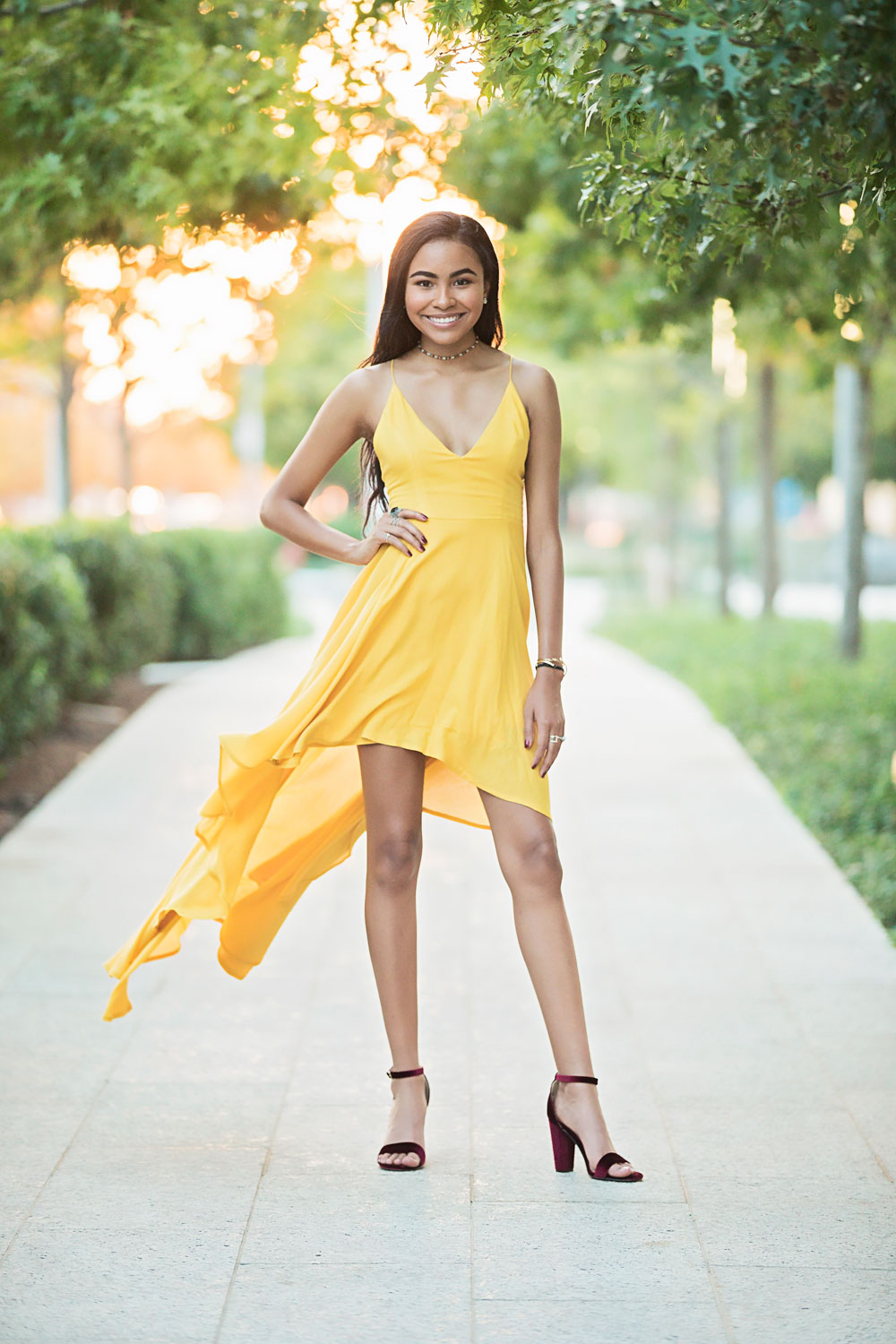 Senior girl wearing long yellow dress, standing on sidewalk with wind blowing dress at the Myriad Gardens in Oklahoma City.
