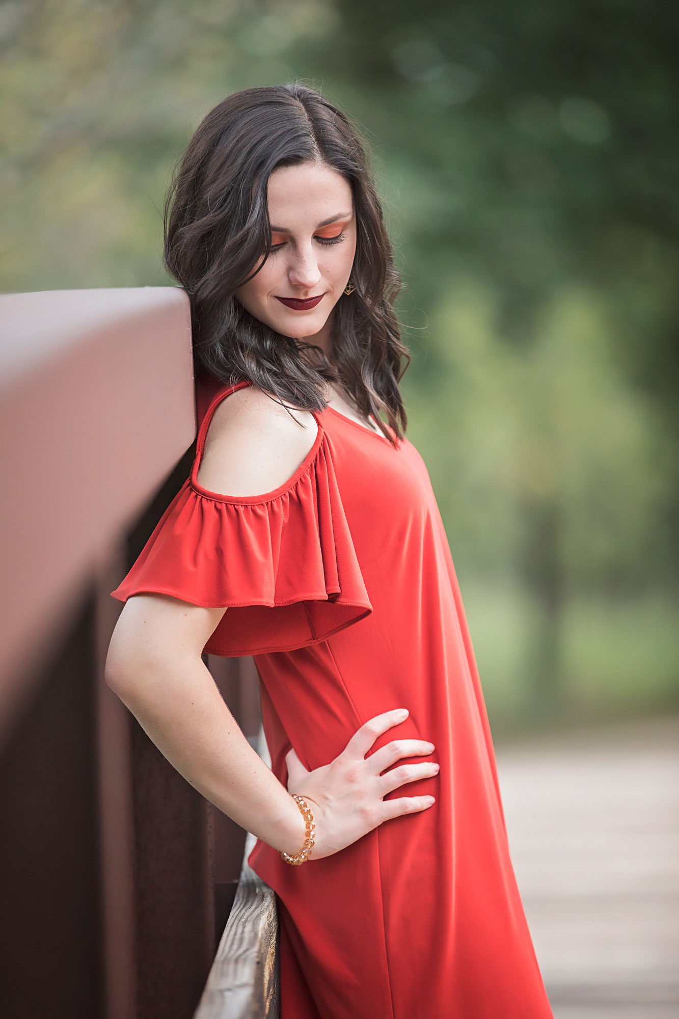 Senior girl wearing orange dress with hand on hip and leaning against a bridge at park in Oklahoma City by Amanda Lynn.