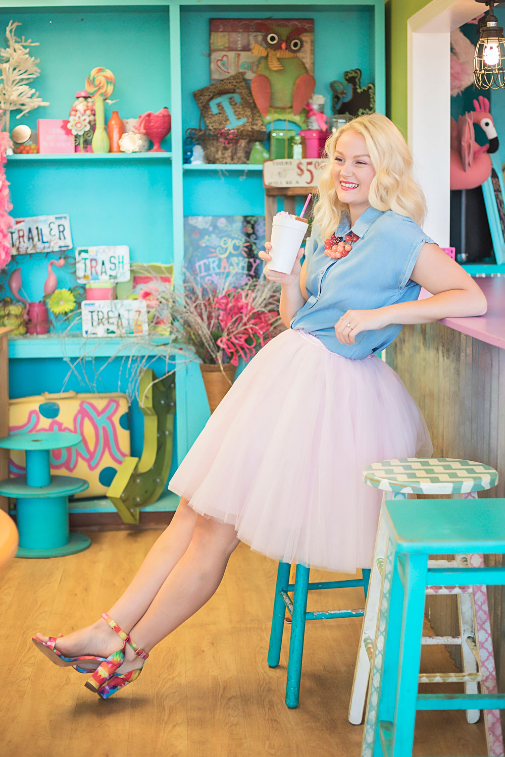 Senior girl wearing pink skirt, leaning against counter at snow cone stand in Oklahoma City.