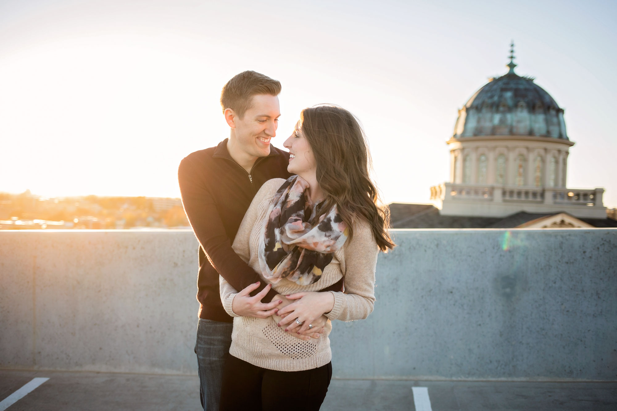 Man wearing dark brown sweater wrapping his arms around woman wearing light brown sweater on top of a parking garage in Oklahoma City, Oklahoma by Amanda Lynn.