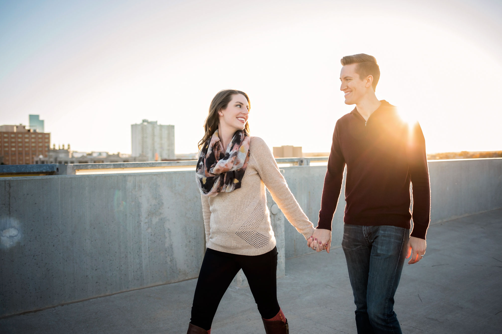 Couple holding hands and woman taking the lead while walking on top of parking garage in downtown Oklahoma City by Amanda Lynn.