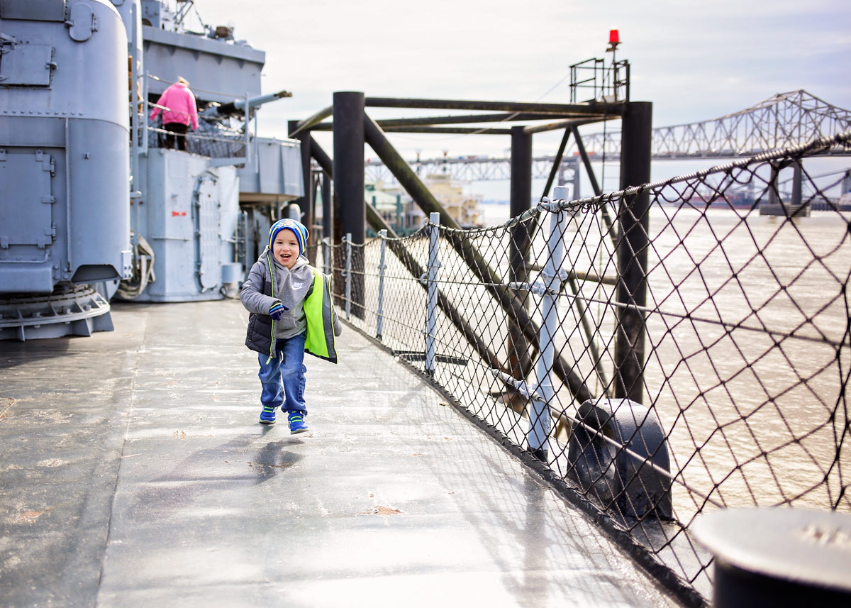 Little boy wearing coat and hat, running on the USS Kidd towards camera in Baton Rouge, LA.