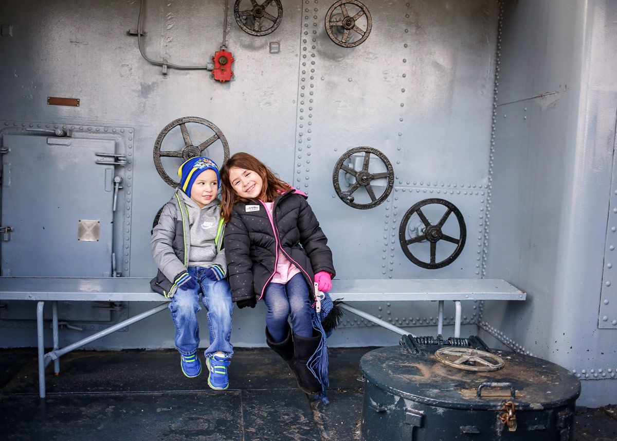 Siblings wearing coats and hats, sitting on bench on the USS Kidd in Baton Rouge.