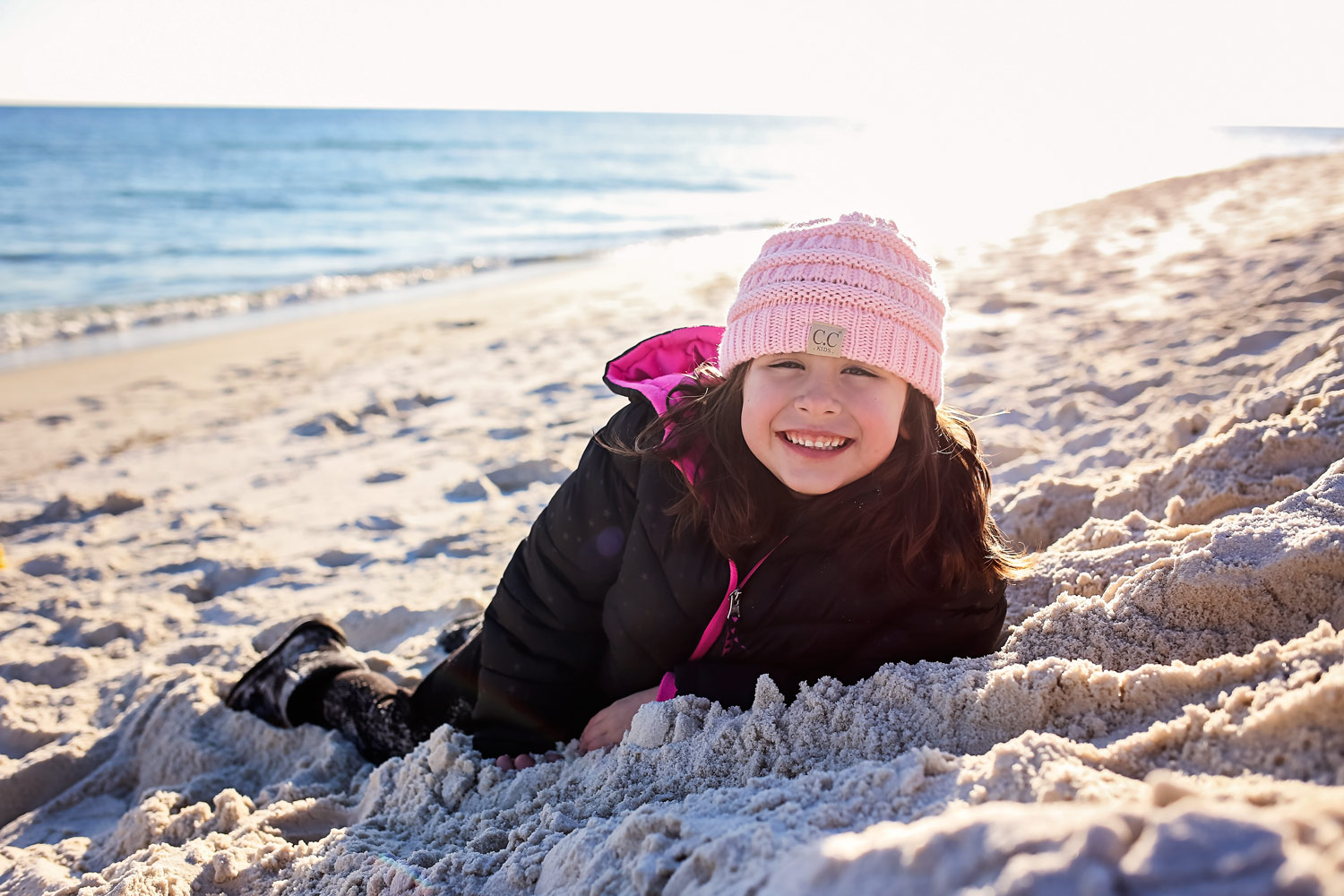 Little girl wearing pink winter hat, laying on the sand at Orange Beach, Alabama.