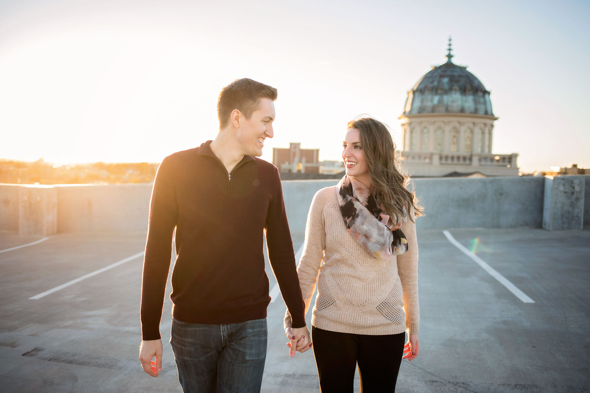 Couple wearing sweaters, holding hands and walking on top level of parking garage in Oklahoma City.