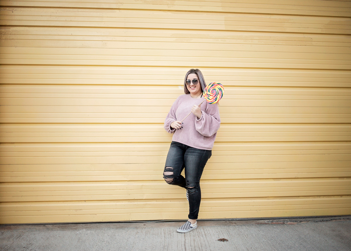 Senior girl with purple hair, wearing a purple shirt and black jeans, leaning against yellow wall and holding a large lollipop in Oklahoma City.