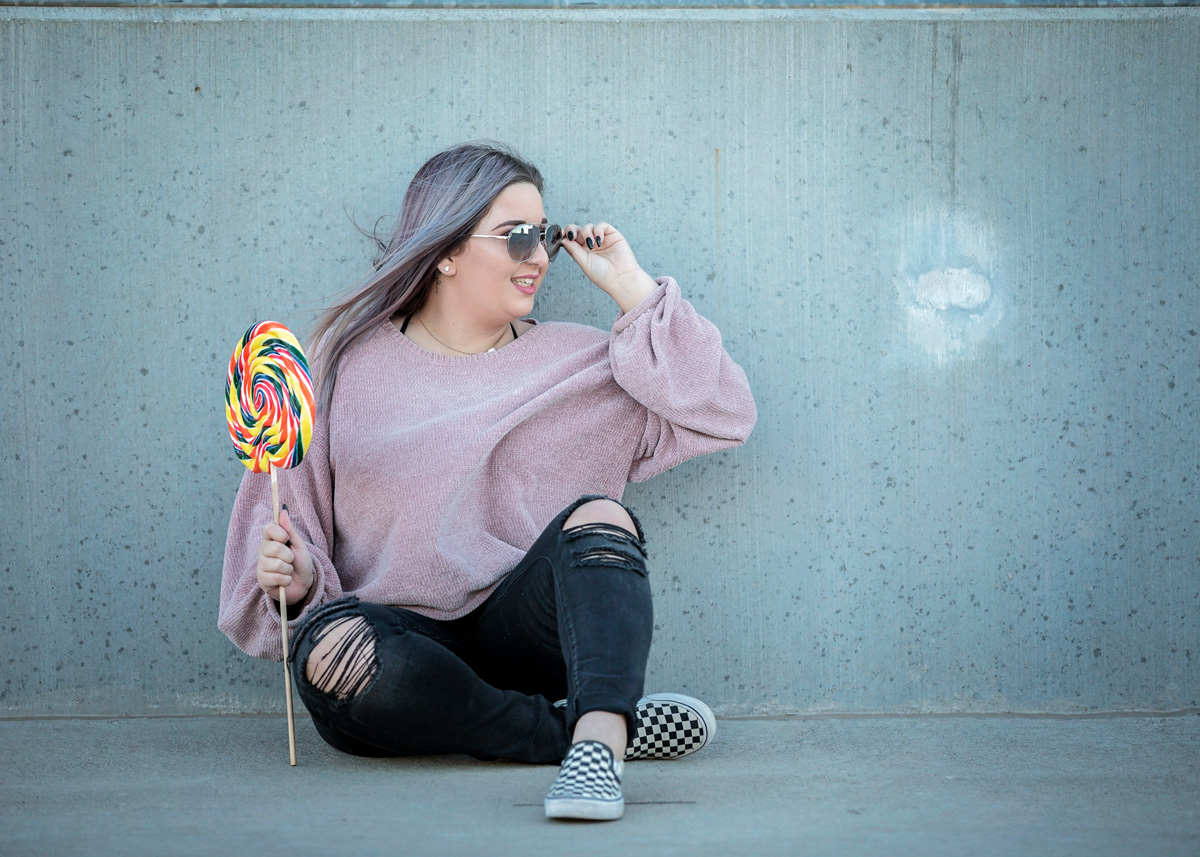 High School Senior girl sitting and looking over sunglasses in Oklahoma City, Oklahoma.