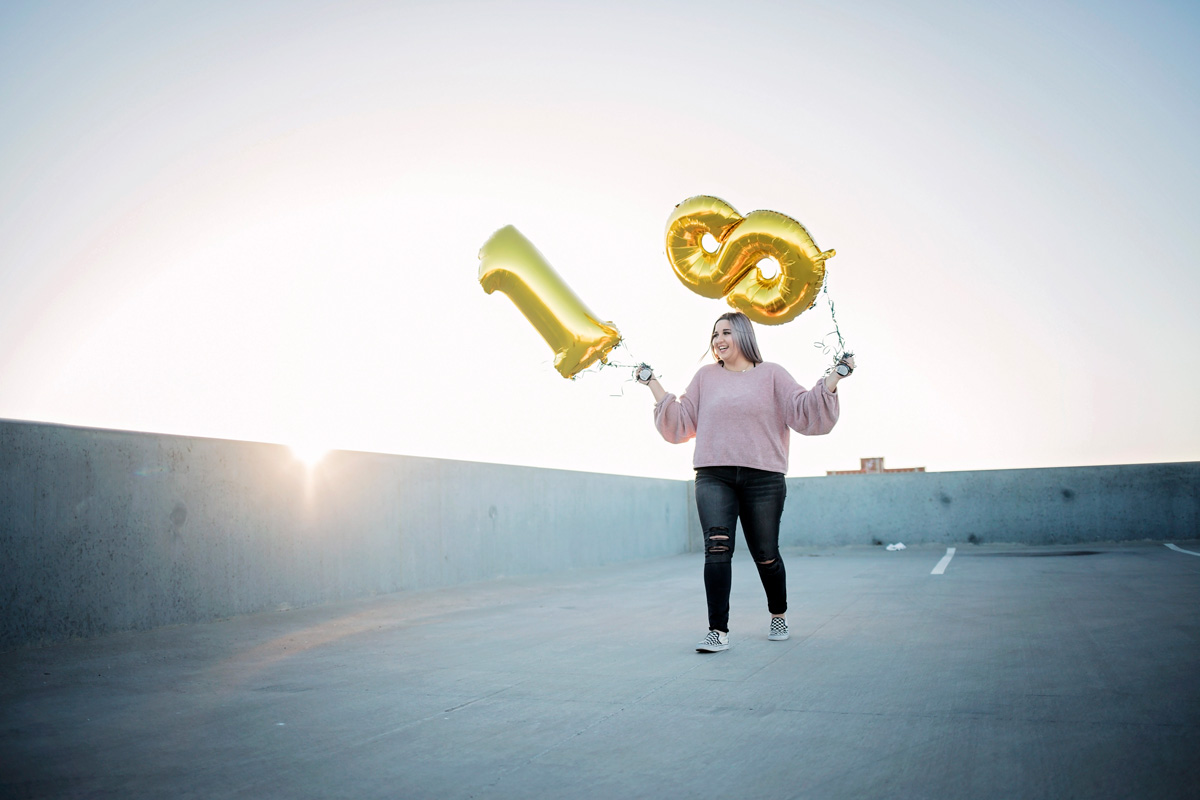 Senior girl wearing purple shirt and black jeans, walking on top of parking garage while holding two giant gold balloons with the sun setting behind her.