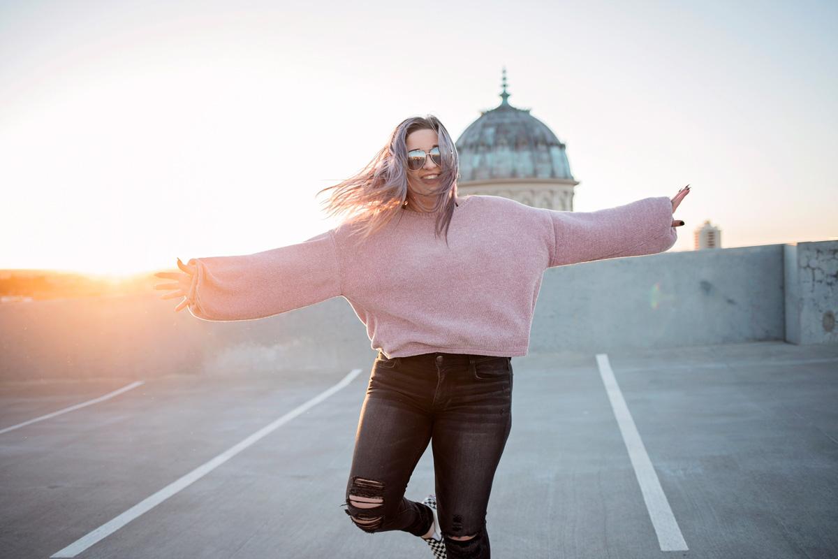 High school senior girl wearing purple sweater, dancing on top of parking garage in downtown Oklahoma City by Amanda Lynn.