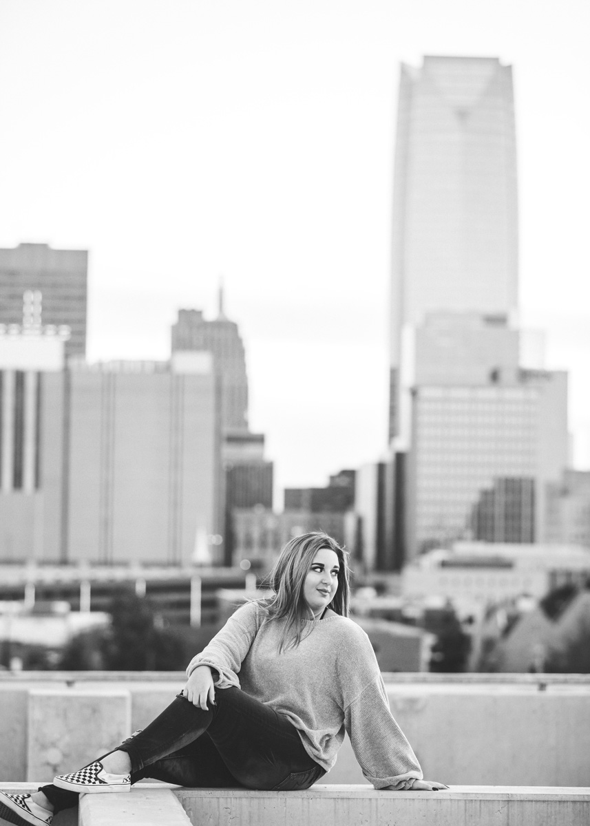 Black and white image of high school senior girl sitting on top of parking garage with downtown Oklahoma City in the background.