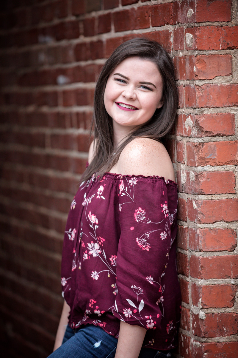 High school senior girl leaning against brick, smiling at camera in Oklahoma City by Amanda Lynn Photography.