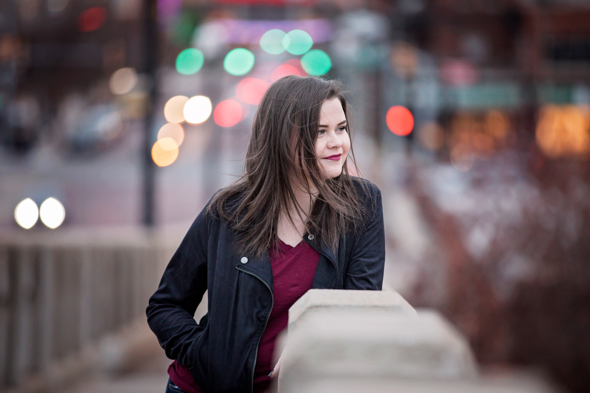 High School Senior girl leaning on concrete bridge, looking camera right, with city lights behind her in Oklahoma City by Amanda Lynn Photography.